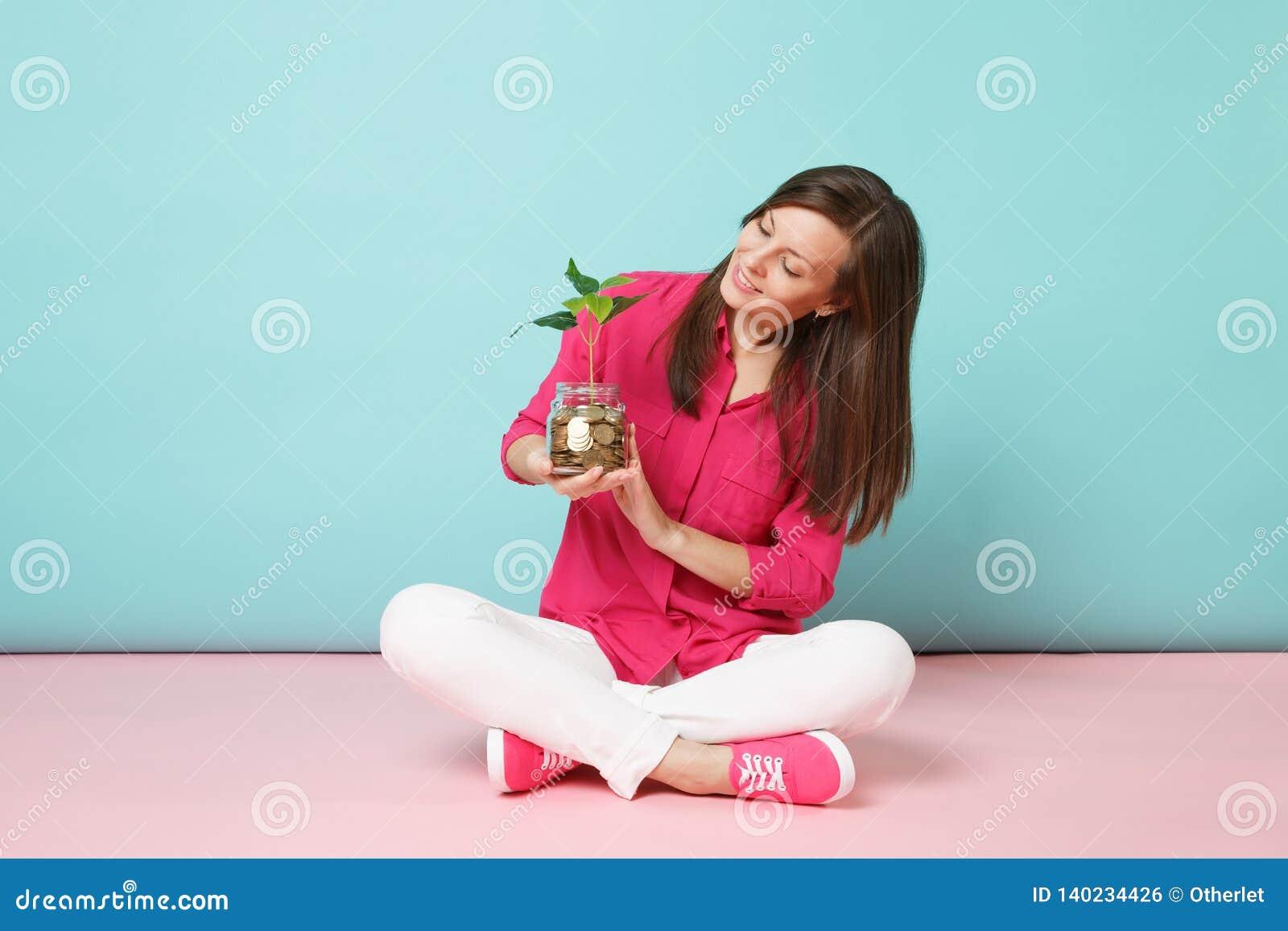 Integrale della donna in camicia rosa, pantaloni bianchi che si siedono sulle monete di oro della tenuta del pavimento in baratto