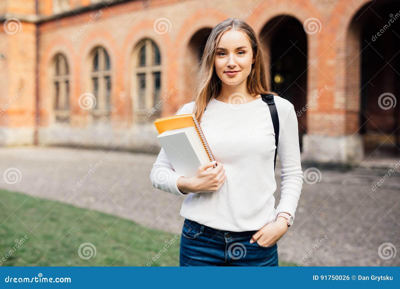 Intelligenter weiblicher Student mit Tasche und Büchern auf dem Campus draußen