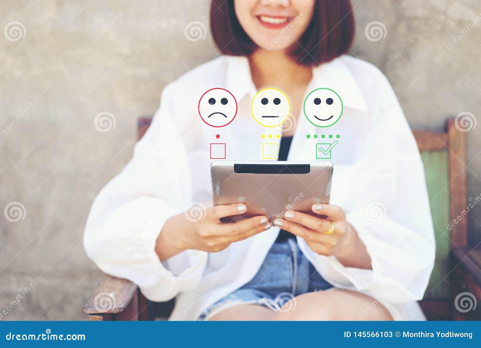 Intelligentes Gerät der Frauenhandholding-Tablette mit dem Einsetzen des Häkchens mit smileygesichtsmarkierung in Kaffeestube, Zu