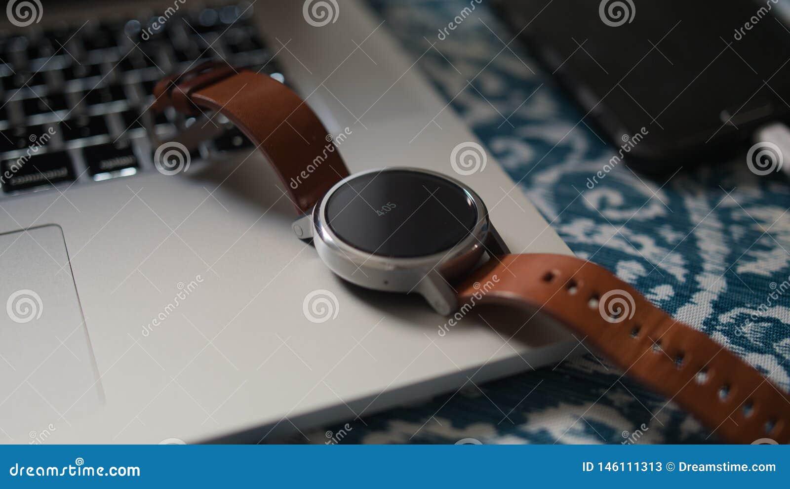 Intelligentes Uhrleder auf Laptop-Computer auf Schreibtisch Smartphone