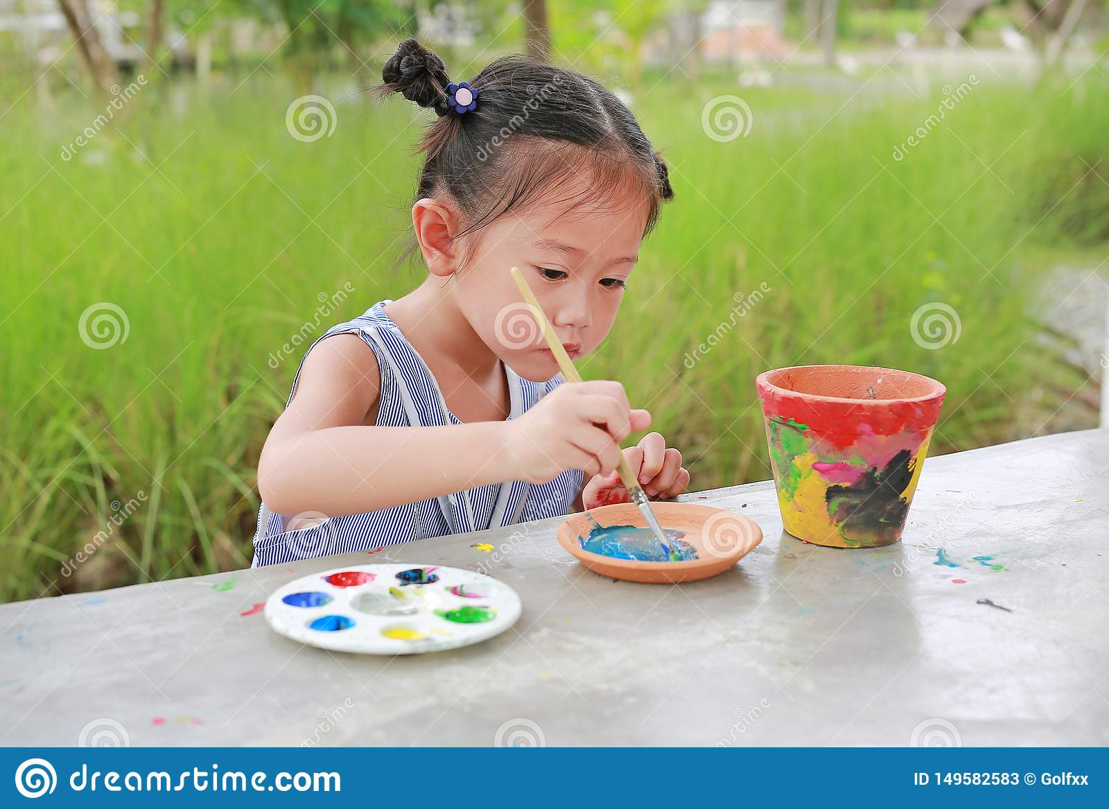 Intend Asian kid girl paint on earthenware dish