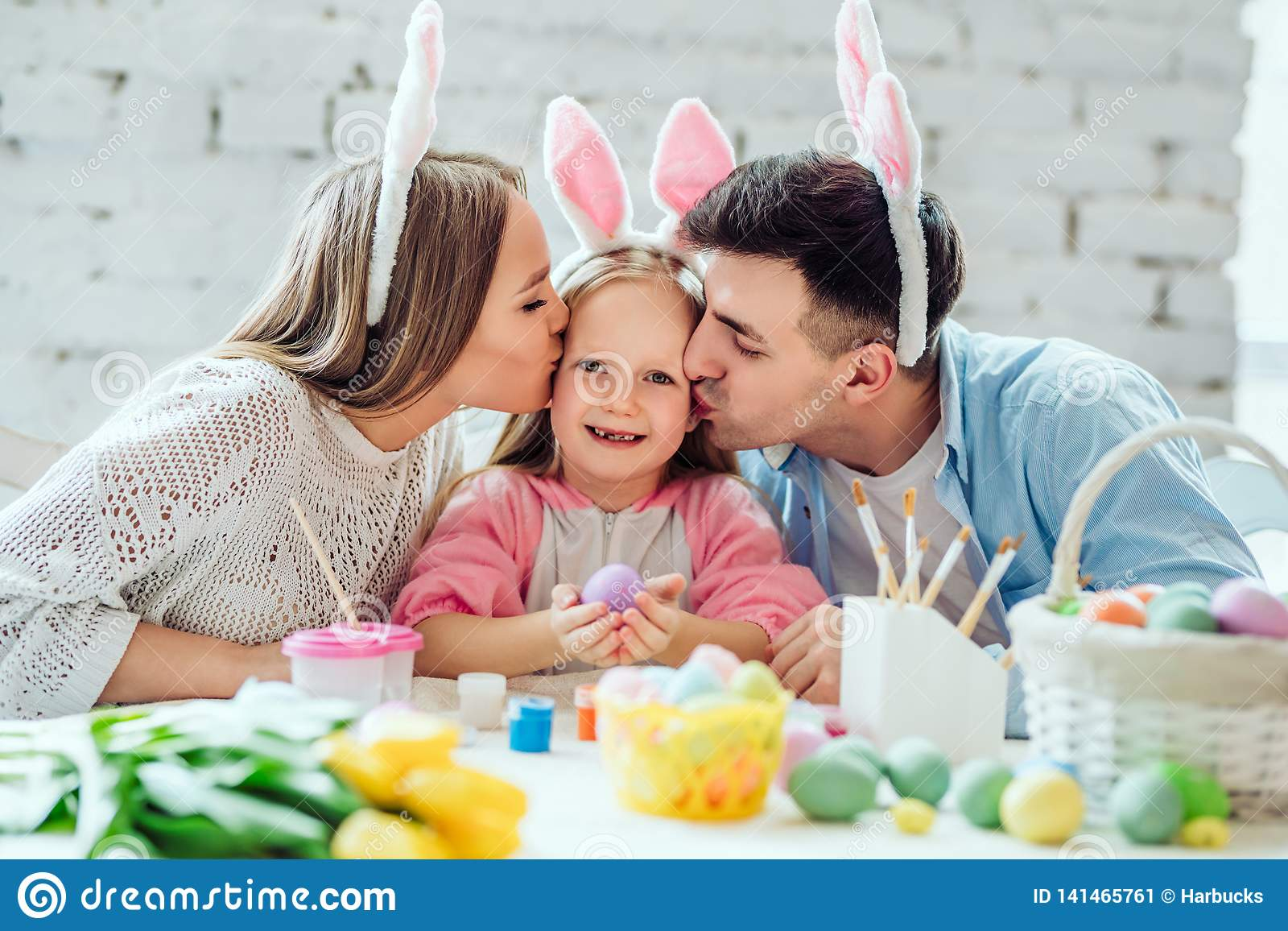 Intentamos hacer un día de fiesta para usted Huevos de Pascua preciosos de la pintura de la familia junto Niña feliz que sostiene