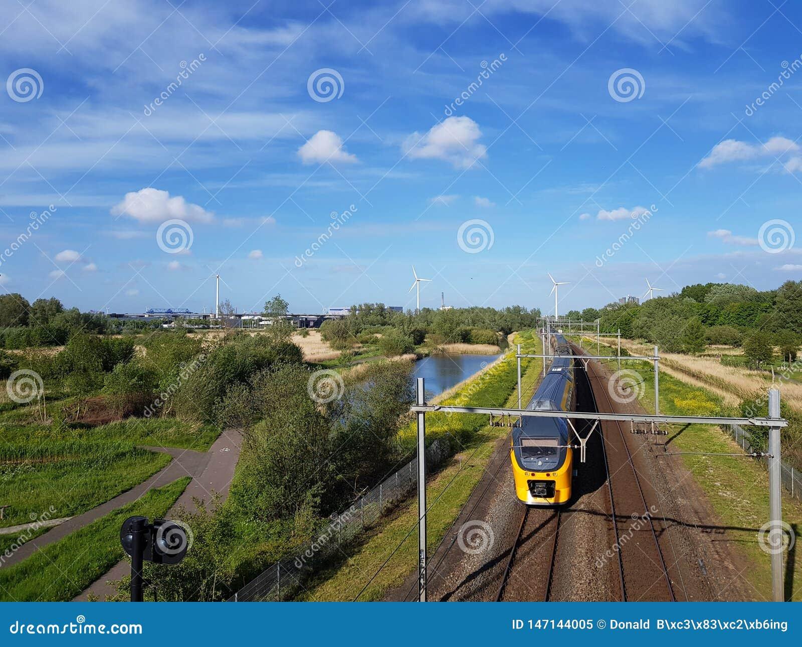 Intercity τραίνο στη διαδρομή σιδηροδρόμων με την αποζημίωση φύσης και ανεμοστρόβιλοι που παράγουν την πράσινη ενέργεια