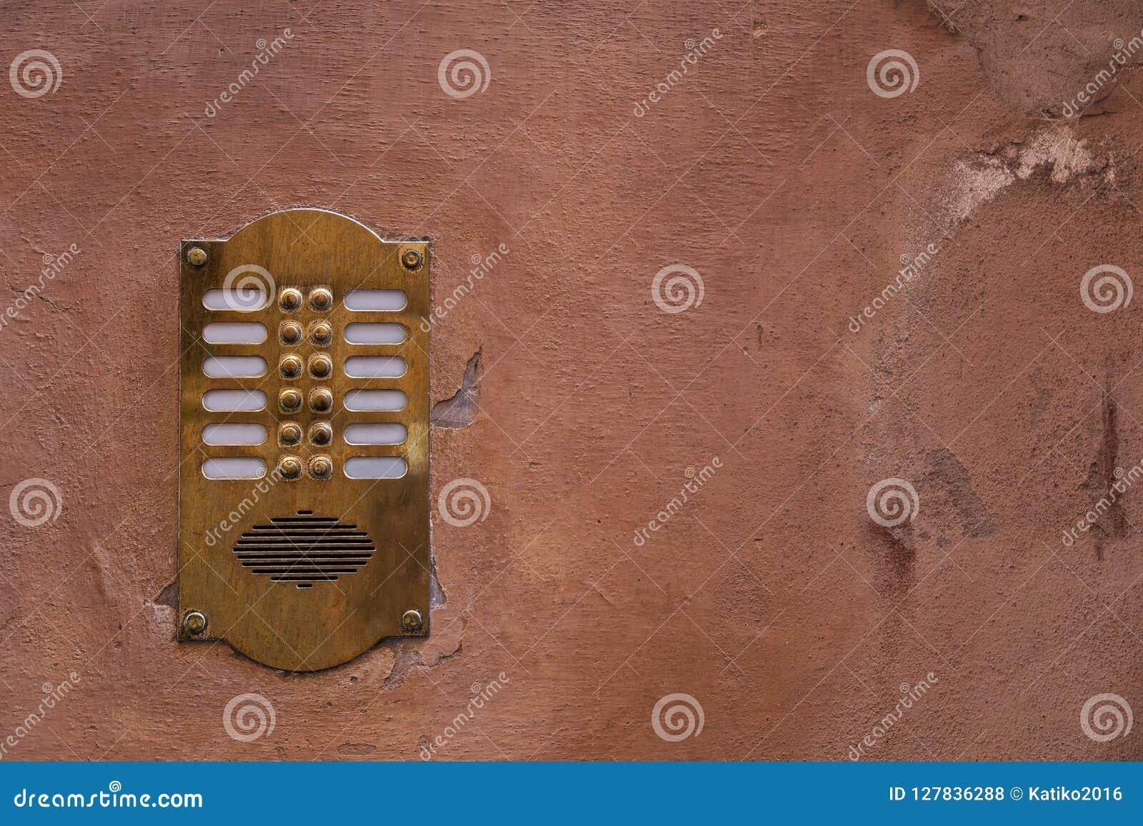 Intercomunicador de bronze velho em uma parede velha com pintura da casca