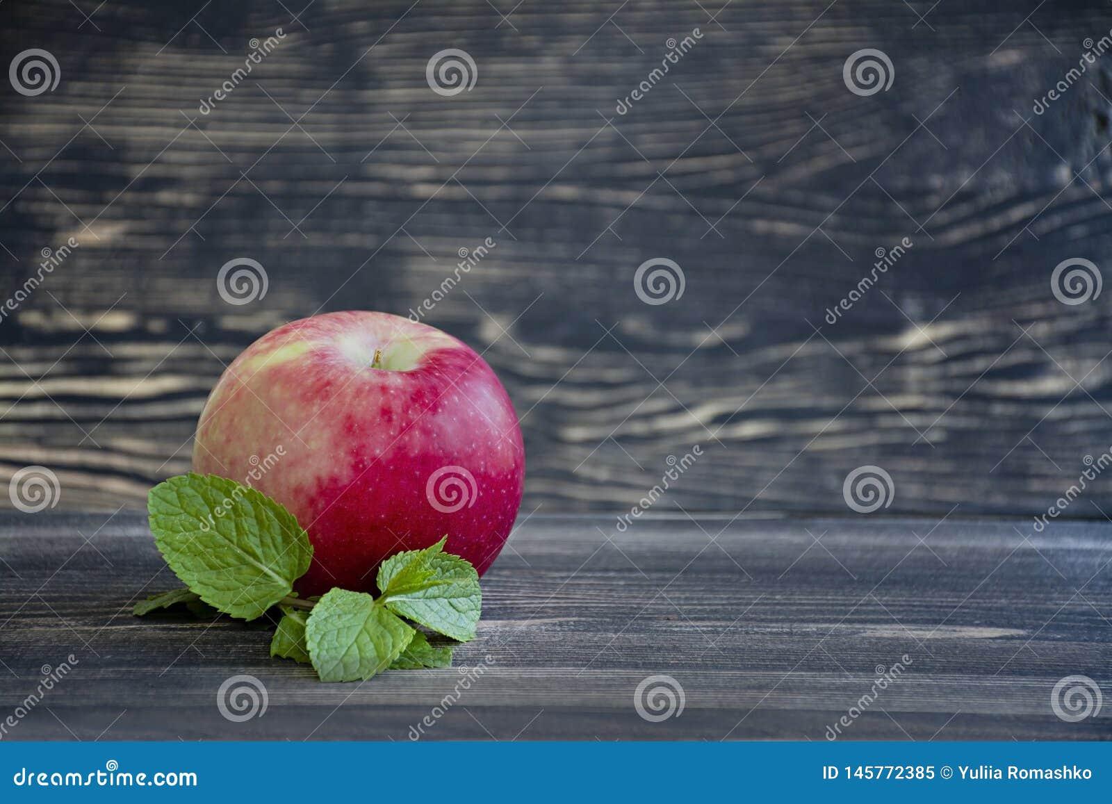 Intere mele fresche con la menta su fondo di legno