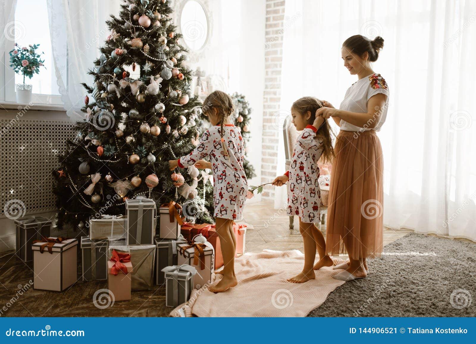 Interessierende Mutter flicht die Borte ihrer kleinen Tochter, während Sekundentochter einen Baum des neuen Jahres im gemütlich