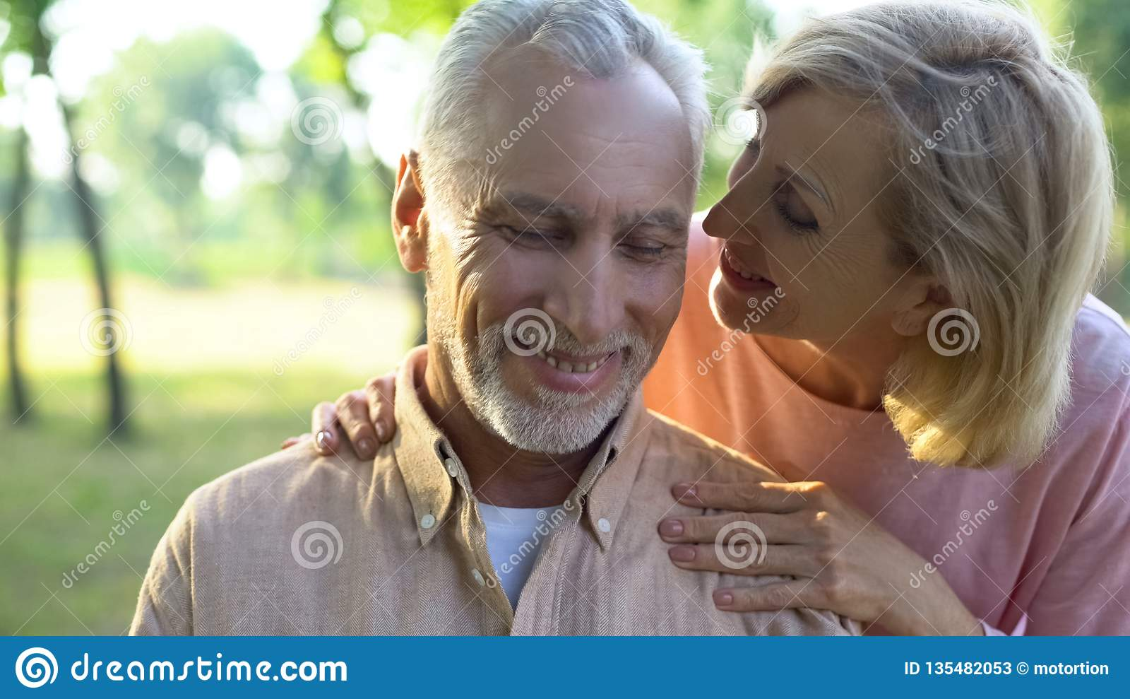 Interessierende reife Frau, die mit hübschem Ehemann im Park, Kompliment flüsternd flirtet