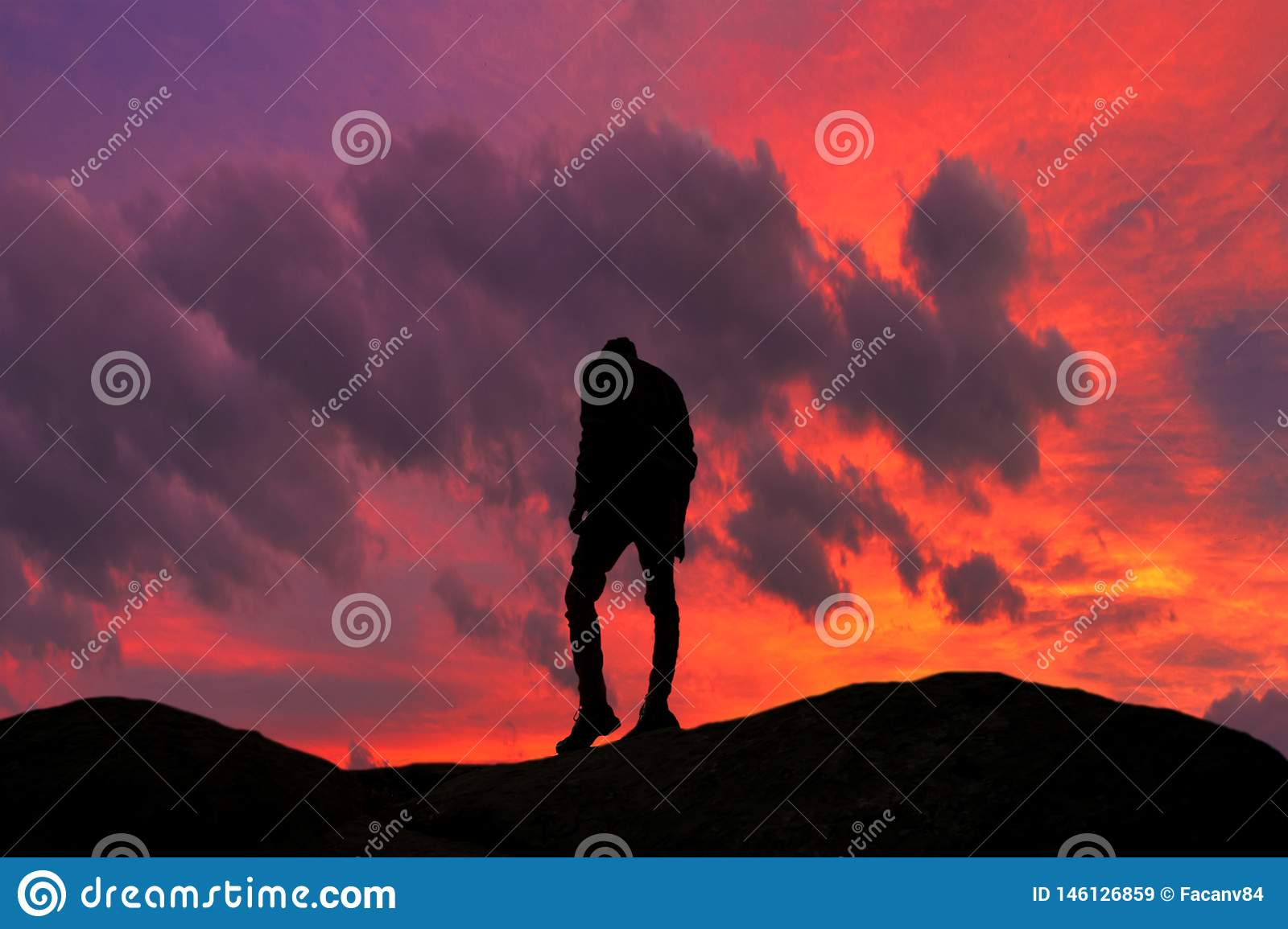 Interesting detail. A silhouette of a young guy climbing to his goal. Very nice sunset and red sky in the background.