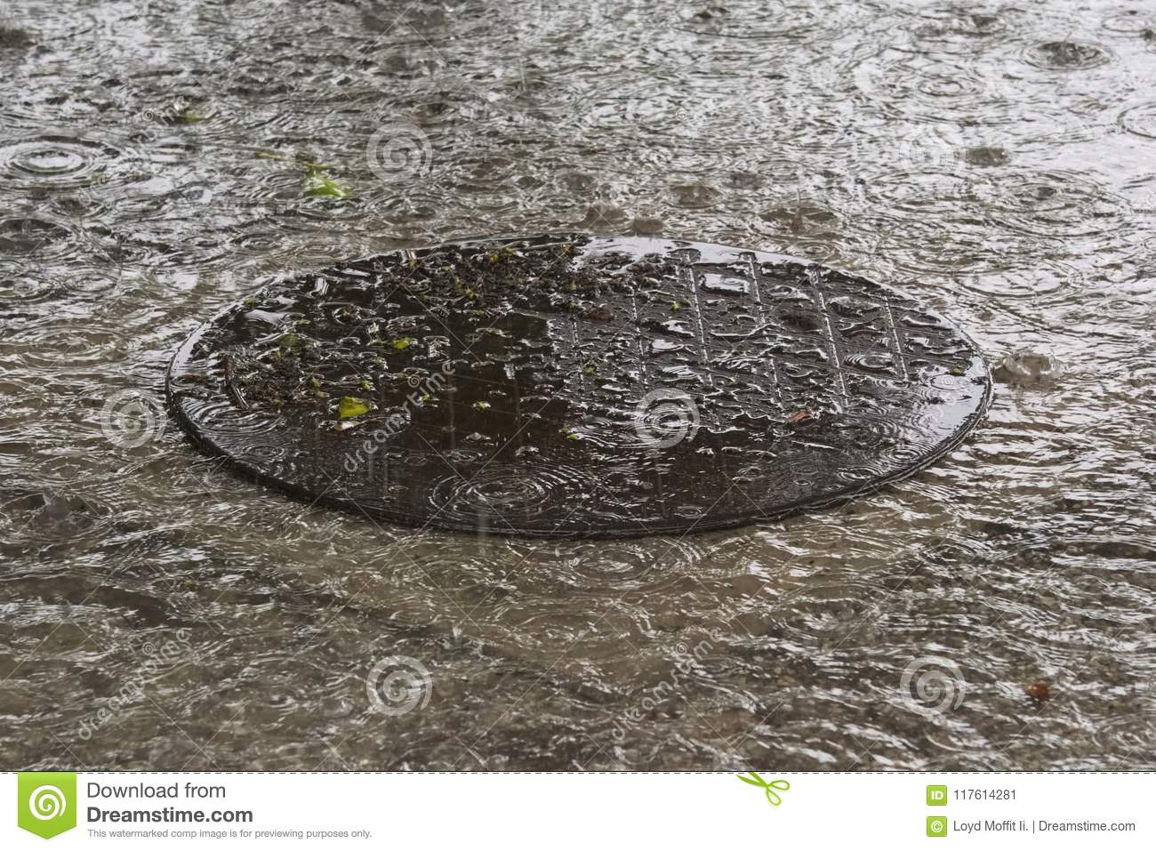 A round, flooded, manhole cover, set during a hard tropical thunderstorm in Thailand.
