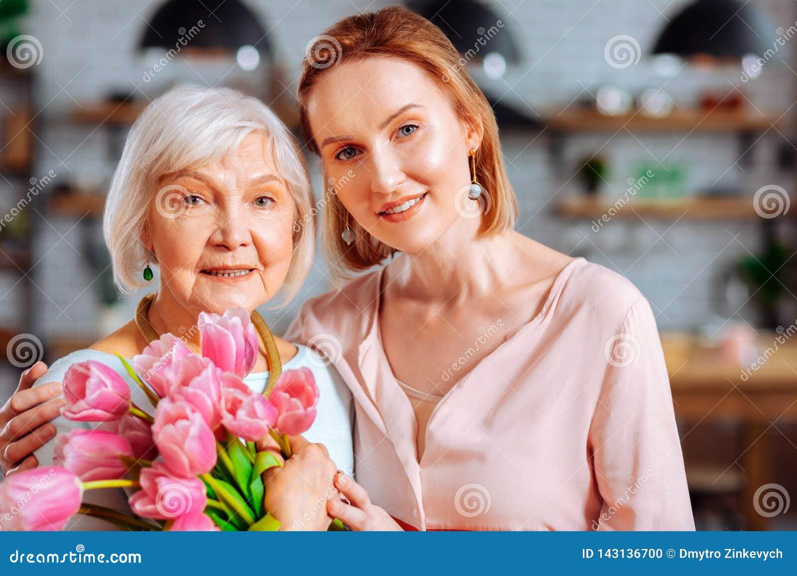 Interesująca dama cuddling starzejącej się mamy z wiązką tulipany