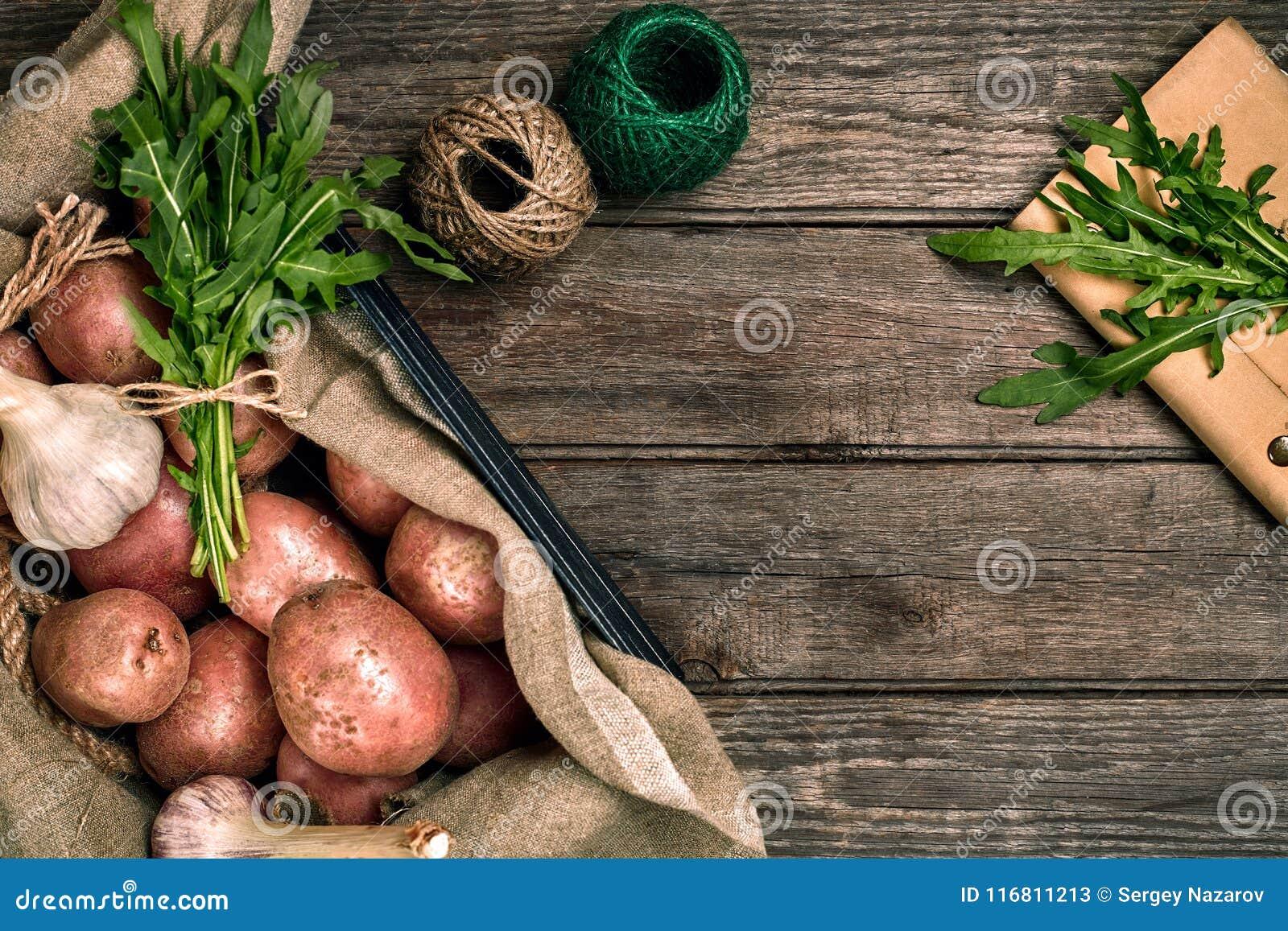 Interi patate, aglio e ruccola organici lavati crudi su tela di sacco sopra il vecchio fondo di legno della plancia Vista superio