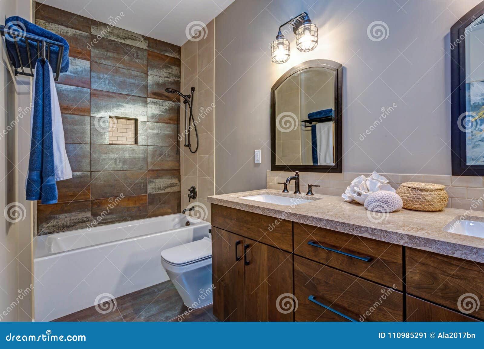Interior à moda do banheiro com o armário dobro da vaidade