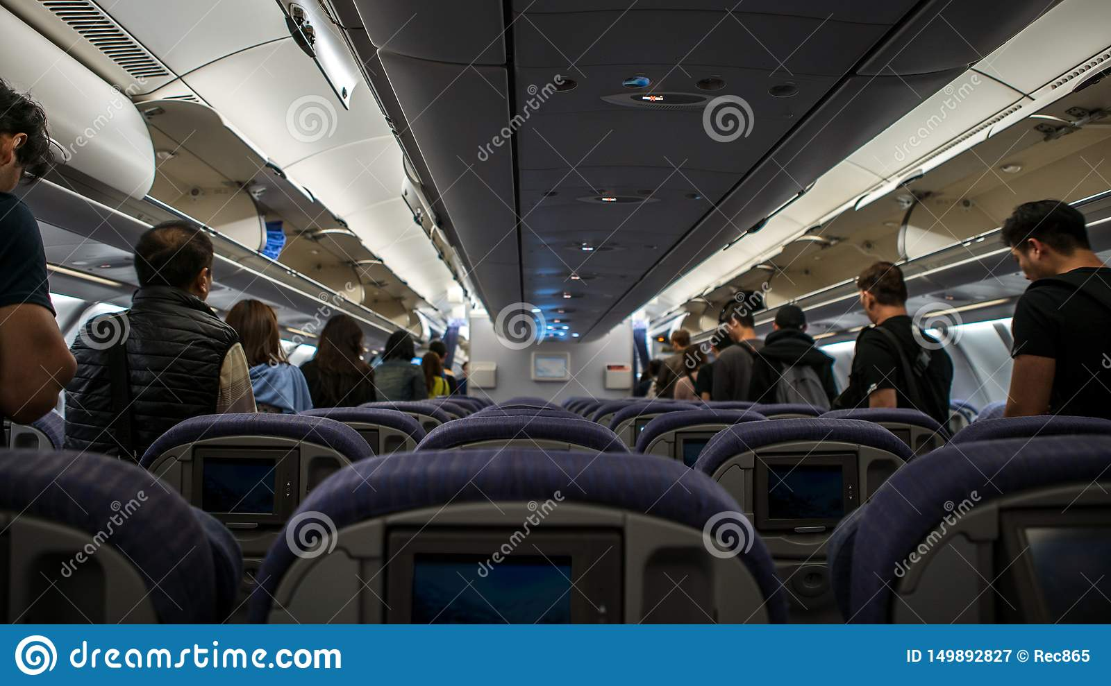 Interior airplane, passengers in aisle are walking to get off airplane
