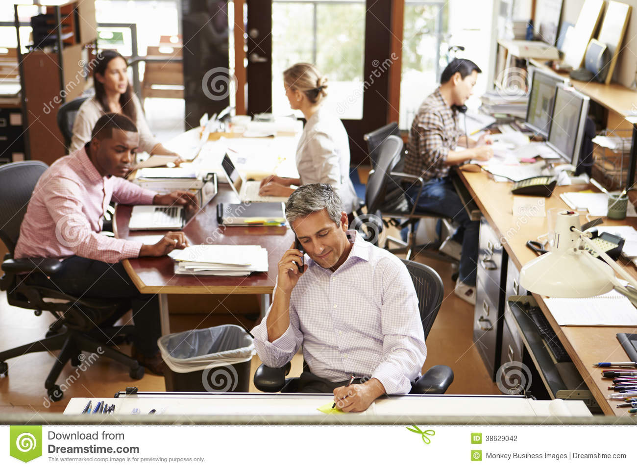 Office With Staff Working At Desks Using Computers And Phones
