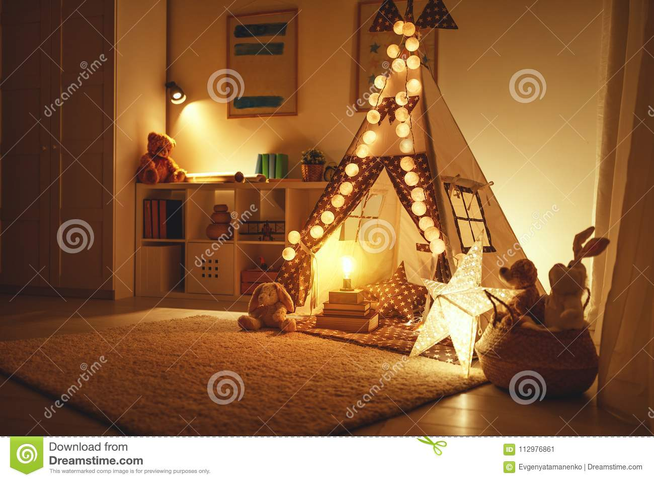 Interior of children`s playroom with tent, lamps and toys in dar