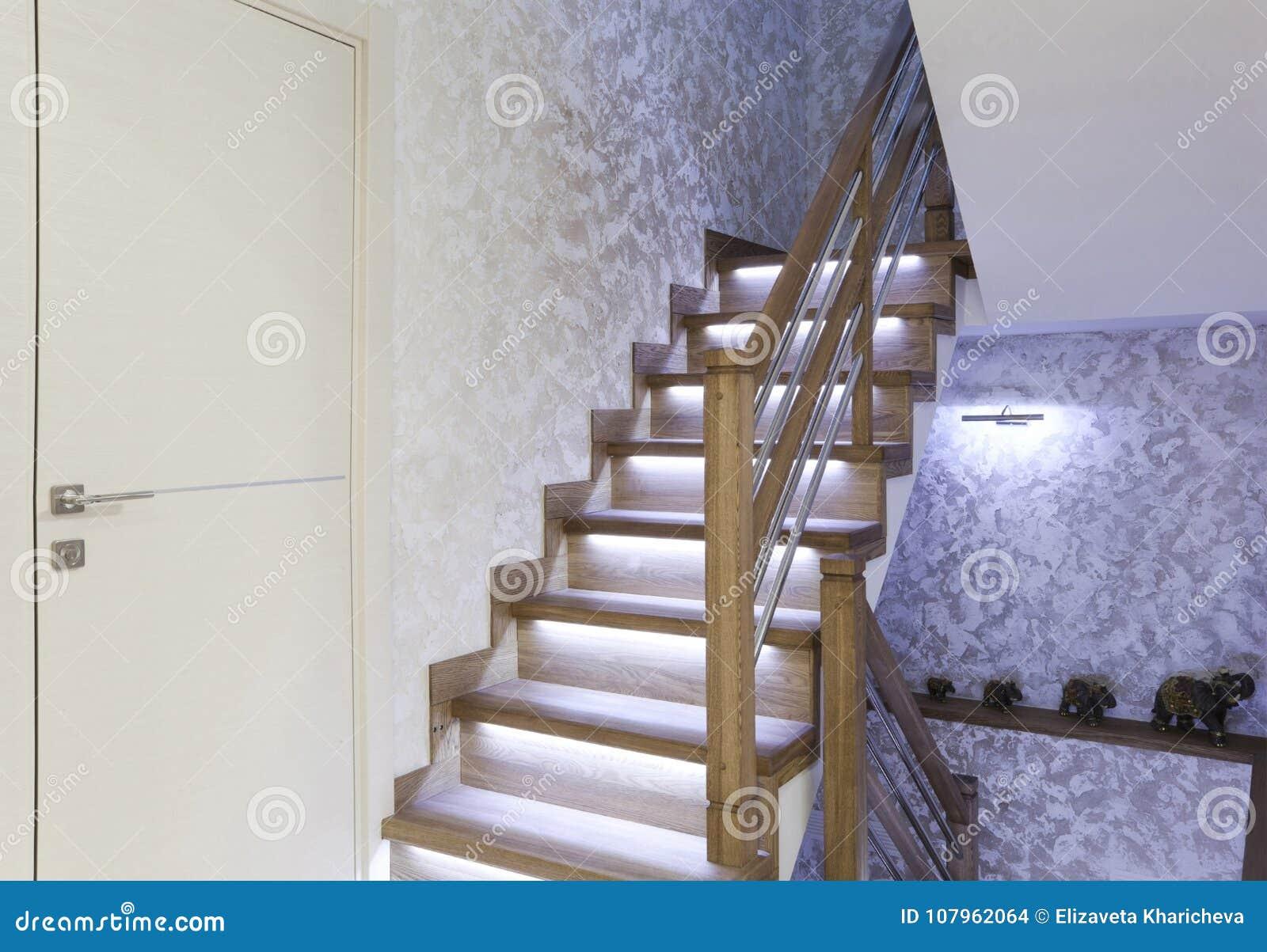 Interior com as escadas do carvalho com o luminoso da iluminação do diodo emissor de luz