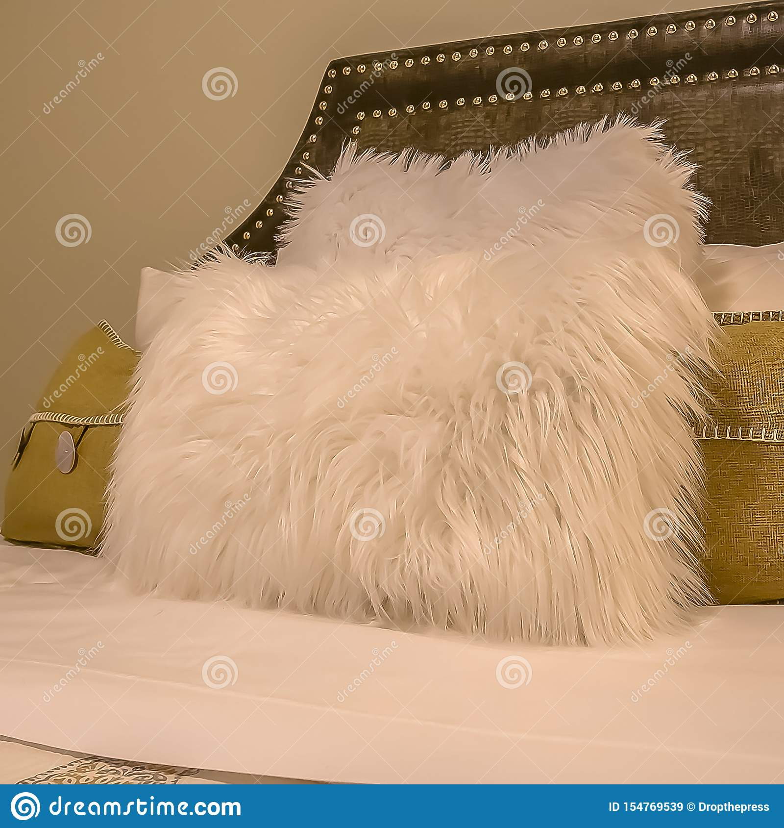 Interior cuadrado del dormitorio con las almohadas contra el cabecero tapizado del belgrave de una cama