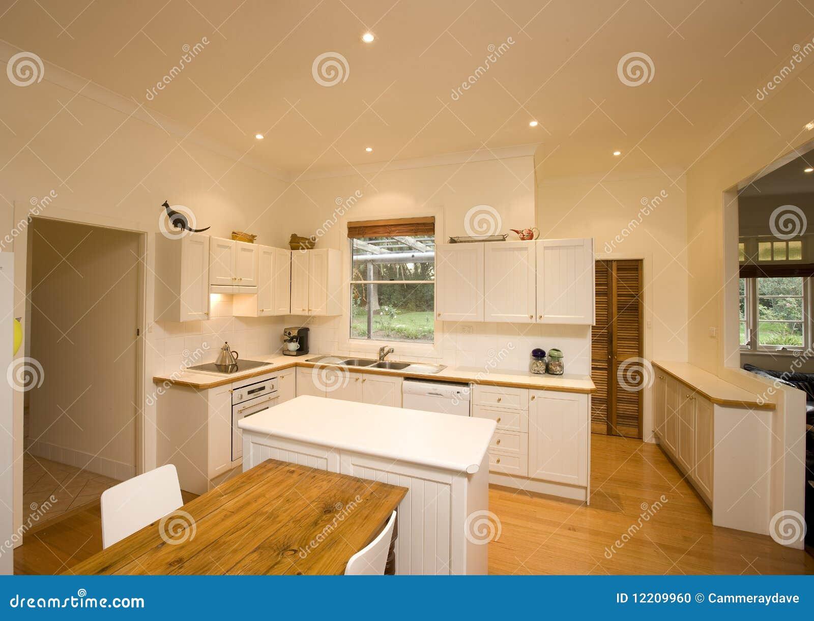 Um interior moderno da cozinha com lotes de paredes leves e brancas. #6D481C 1300 1009
