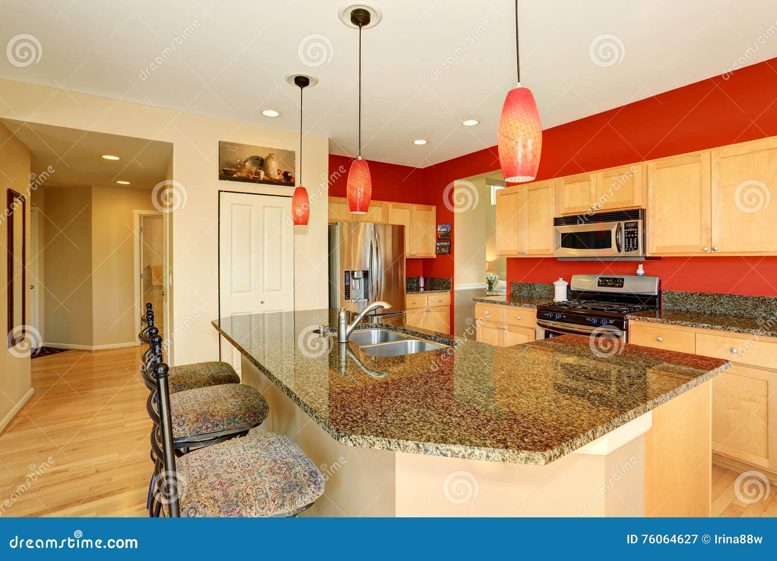 Interior da sala da cozinha com parede vermelha, parte superior contrária do granito e ilha