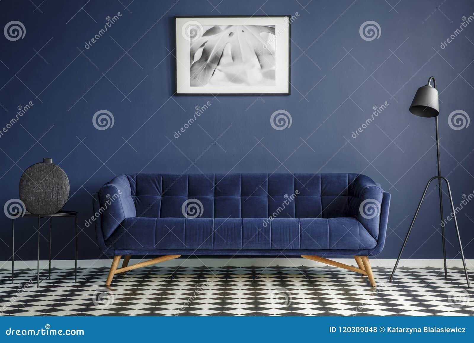 Interior da sala dos azuis marinhos com o sofá confortável do luxuoso no midd