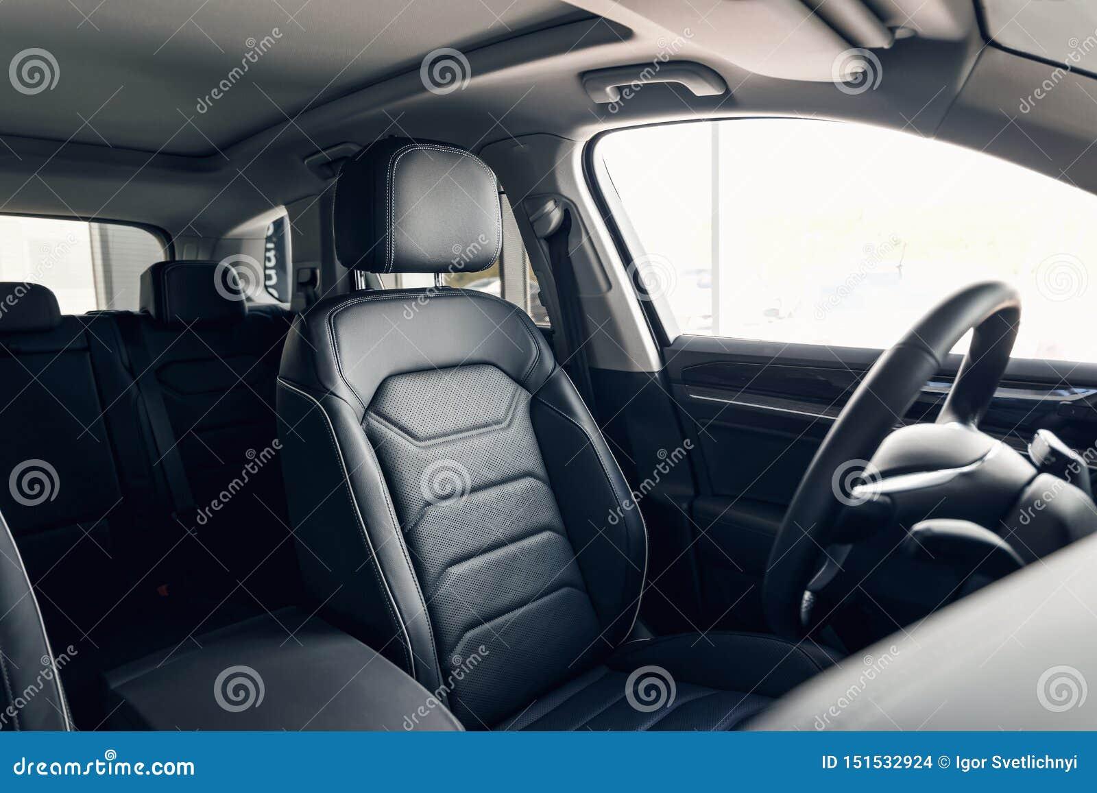 Interior de cuero negro del coche Tablero de instrumentos del coche moderno y volante interiores Interior de cuero perforado del