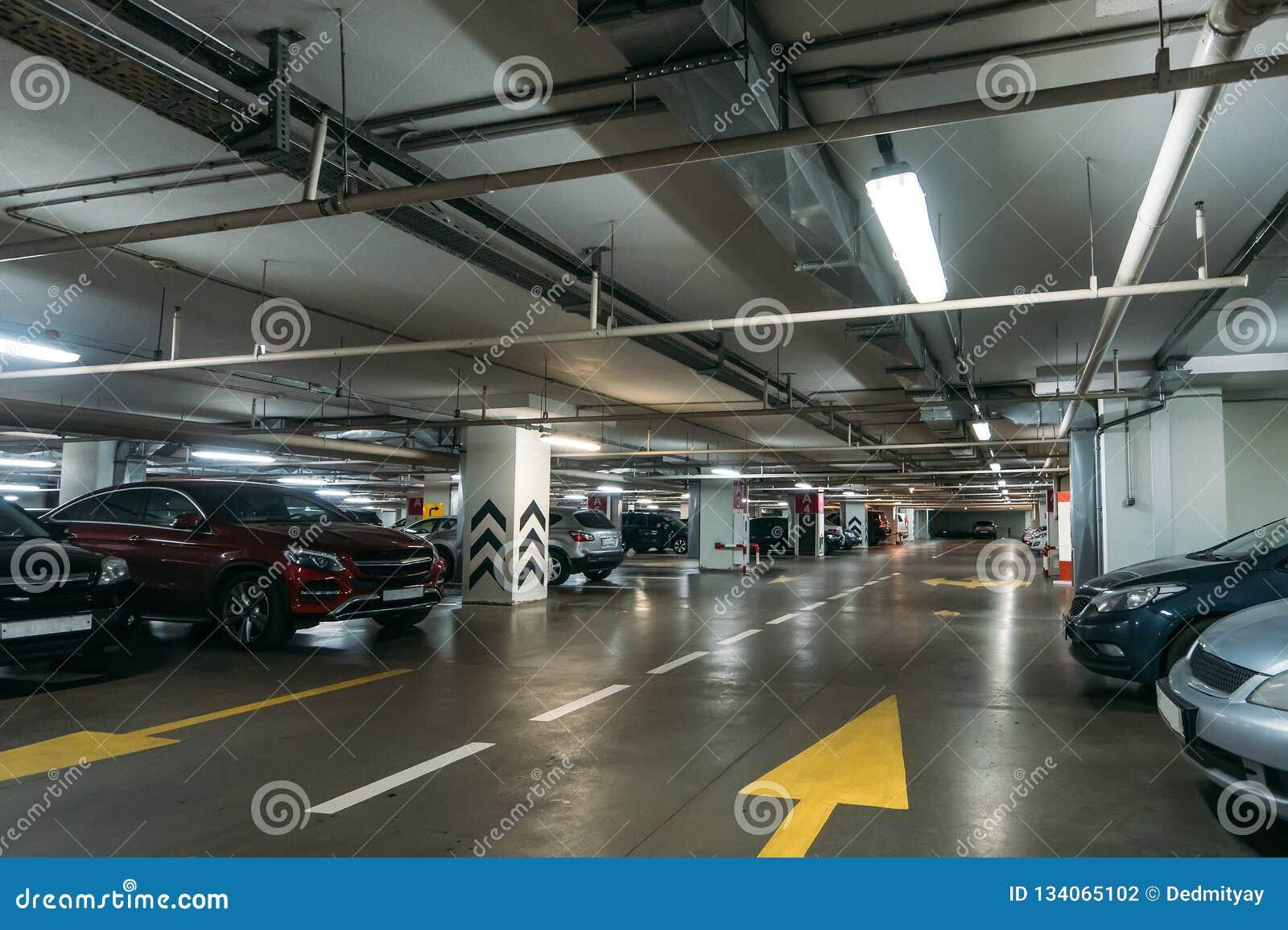 Interior de estacionamento iluminado do carro subterrâneo sob a alameda moderna com lotes dos veículos e das setas no assoalho