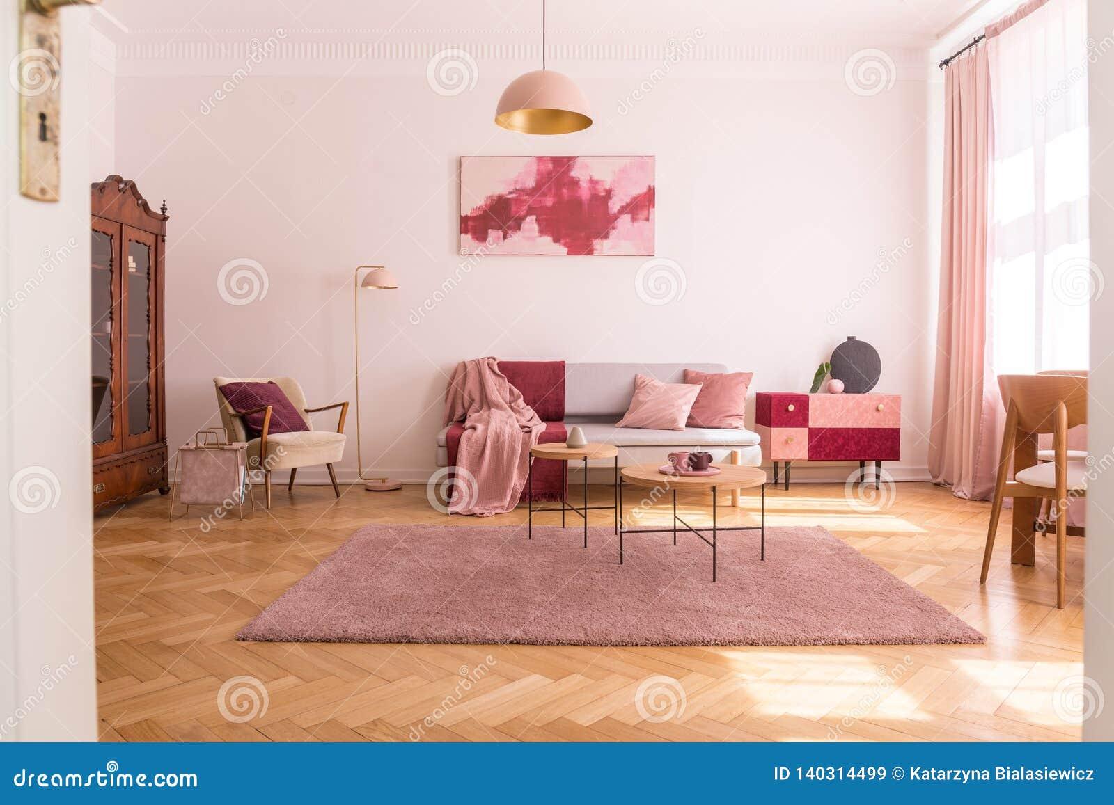 Interior de moda de la sala de estar con el sofá gris con las almohadas rosadas y manta en colores pastel, butaca beige elegante