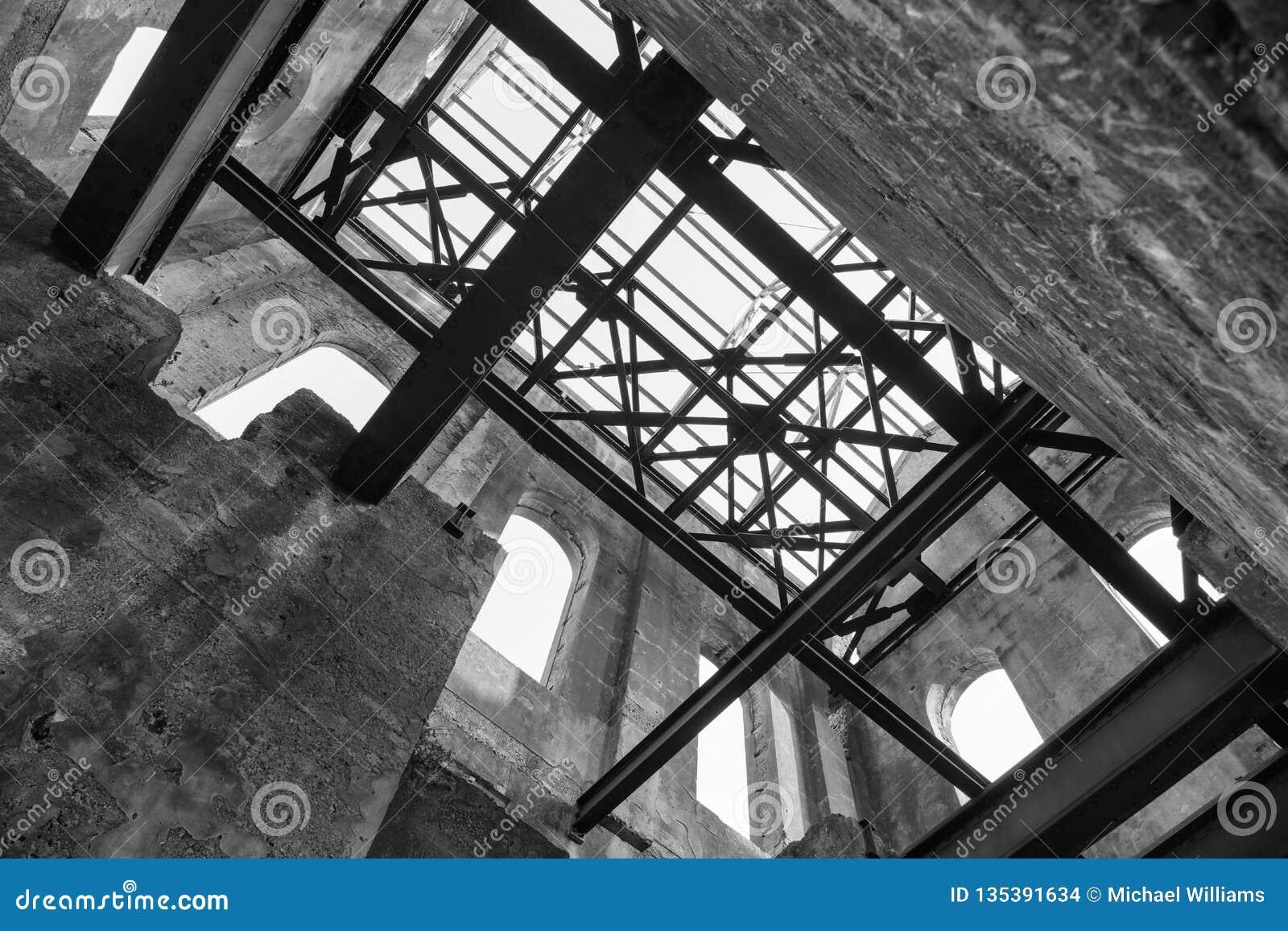 Interior de uma construção industrial velha arruinada, olhando acima em vigas do telhado