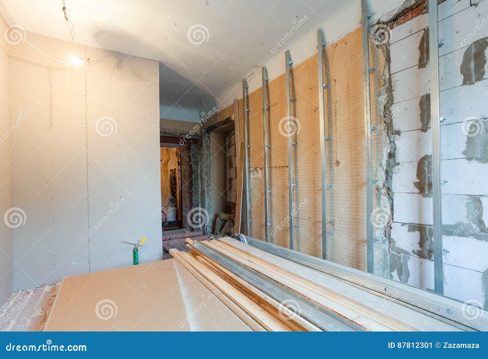 Interior del apartamento con los materiales durante en la renovación que hace la pared del cartón yeso del yeso