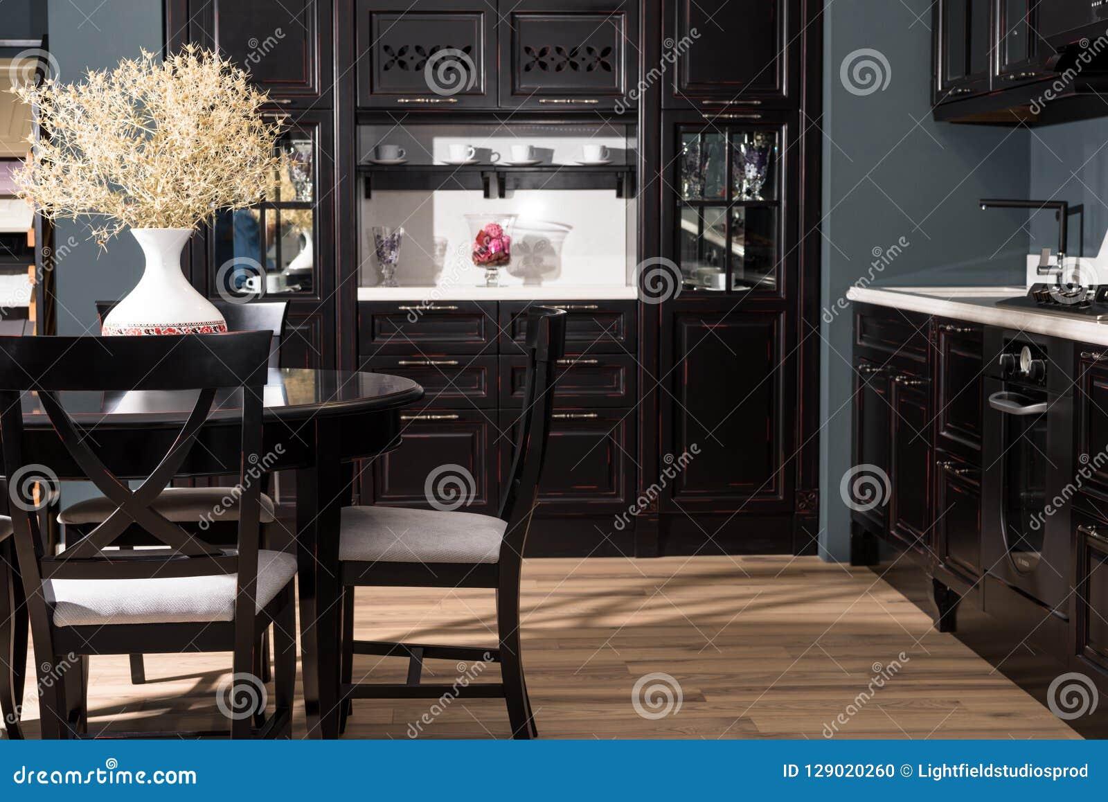 Interior del comedor moderno con muebles y el florero negros de flores secadas