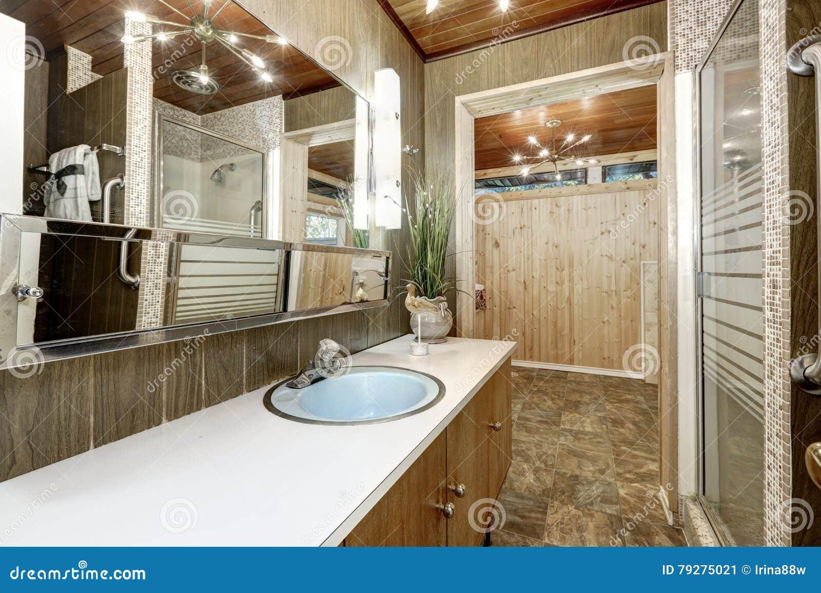 interior del cuarto de bao con las paredes de madera y el suelo de baldosas marrn