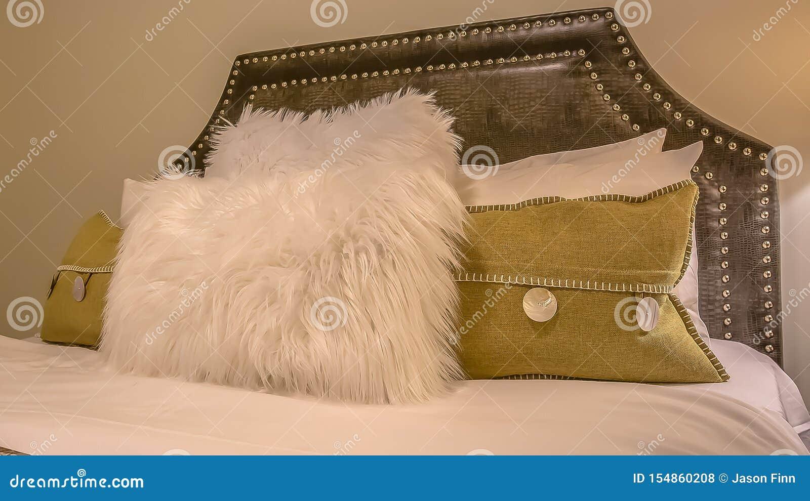 Interior del dormitorio del marco del panorama con las almohadas contra el cabecero tapizado del belgrave de una cama