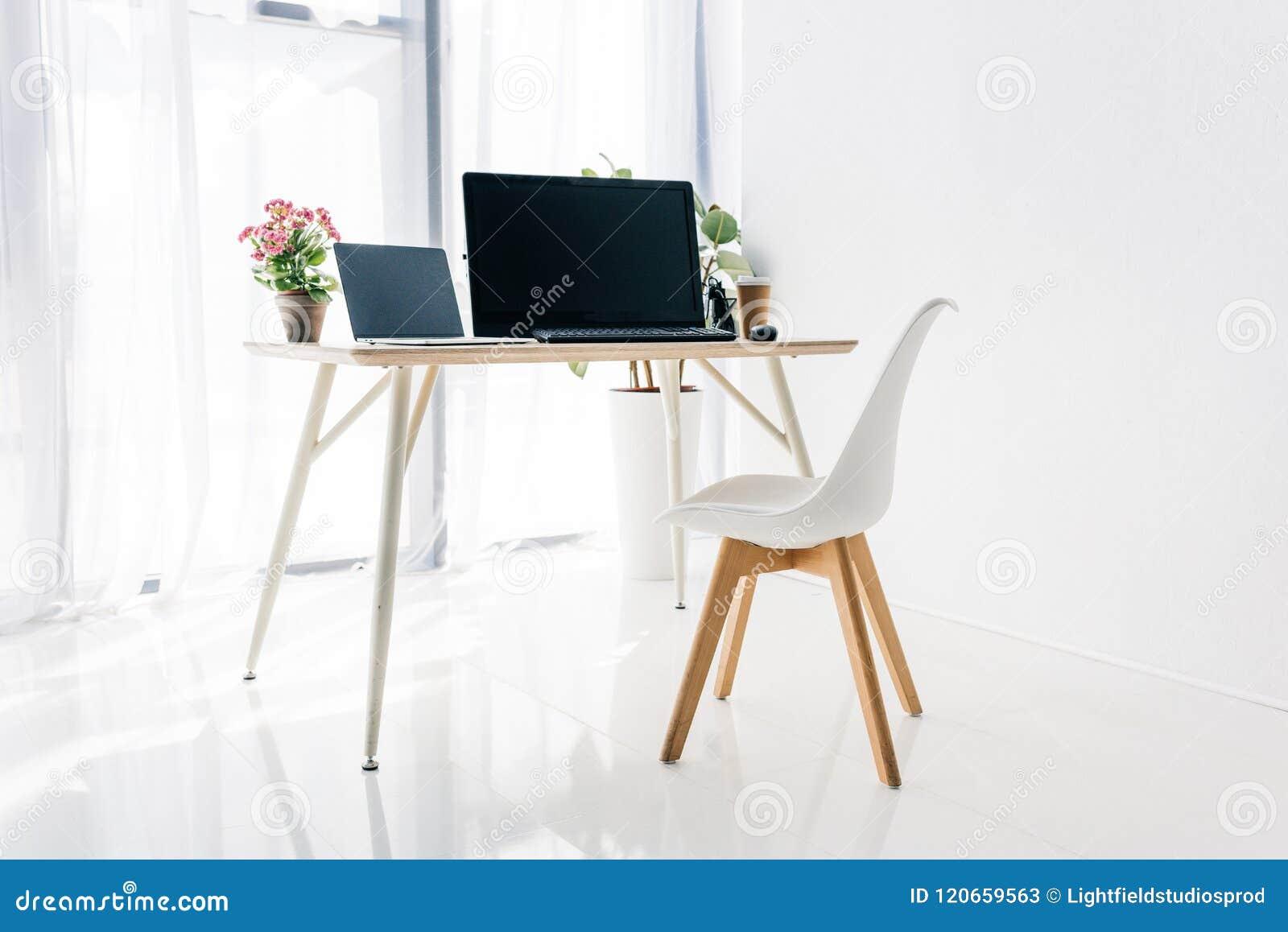 Interior del lugar de trabajo con la silla, las plantas en conserva, el ordenador portátil y el ordenador
