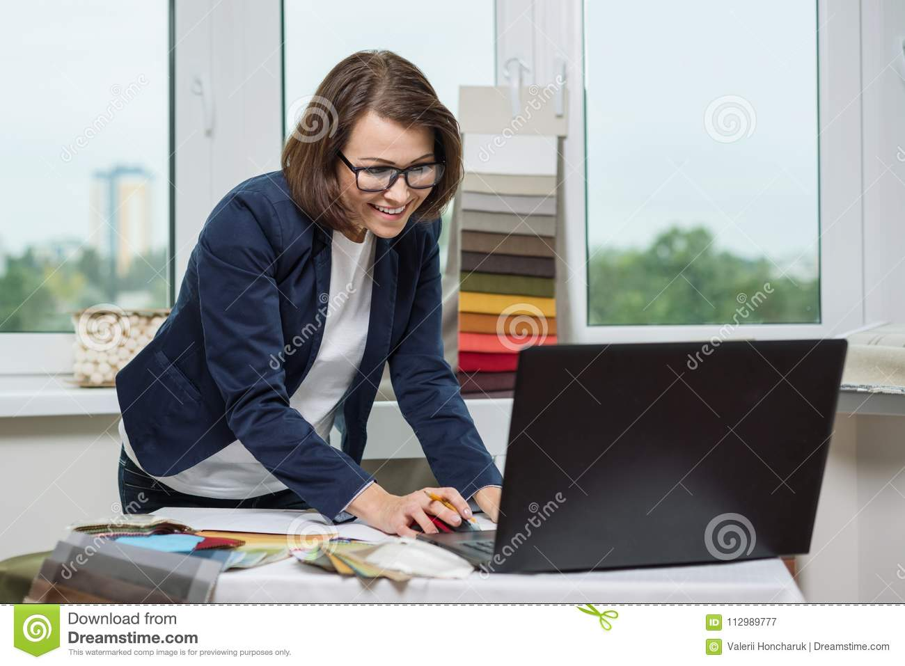 The interior designer, at the workplace in the office, communicates with customers on video communications. Discusses samples of f