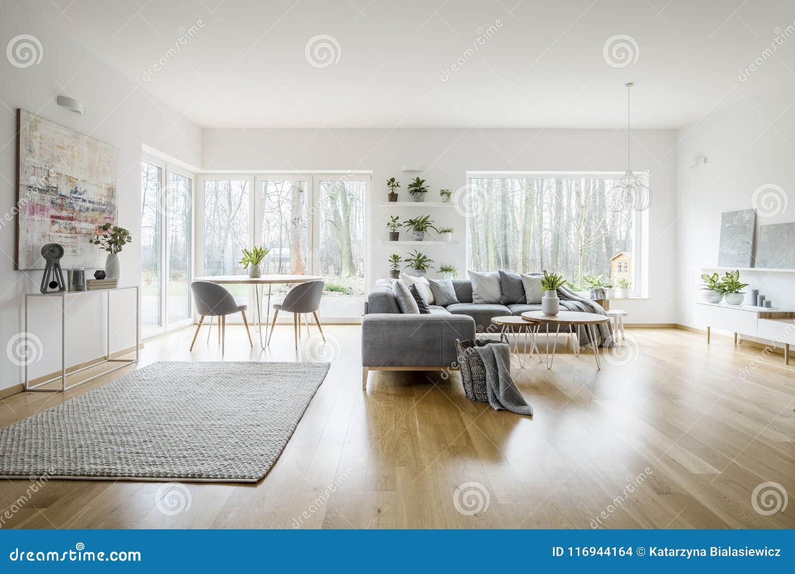 Interior elegante branco da sala de visitas com janelas