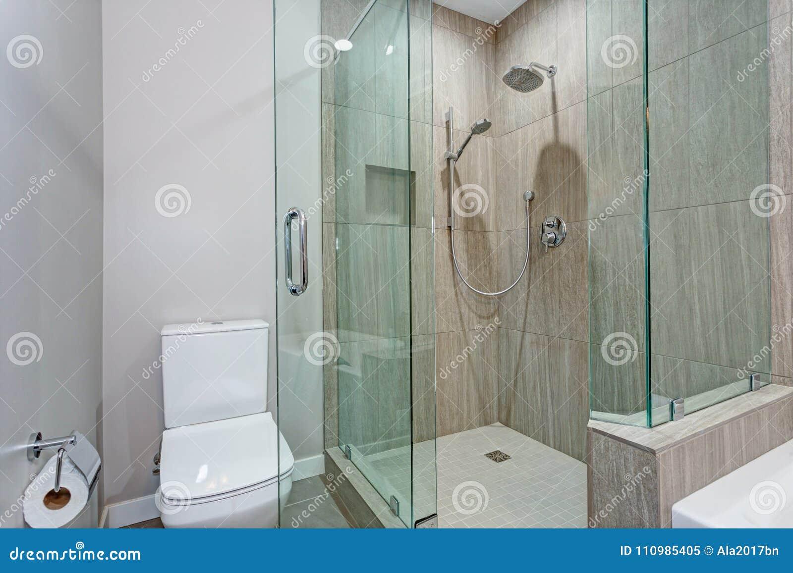 Interior elegante del cuarto de baño con el paseo de cristal en ducha