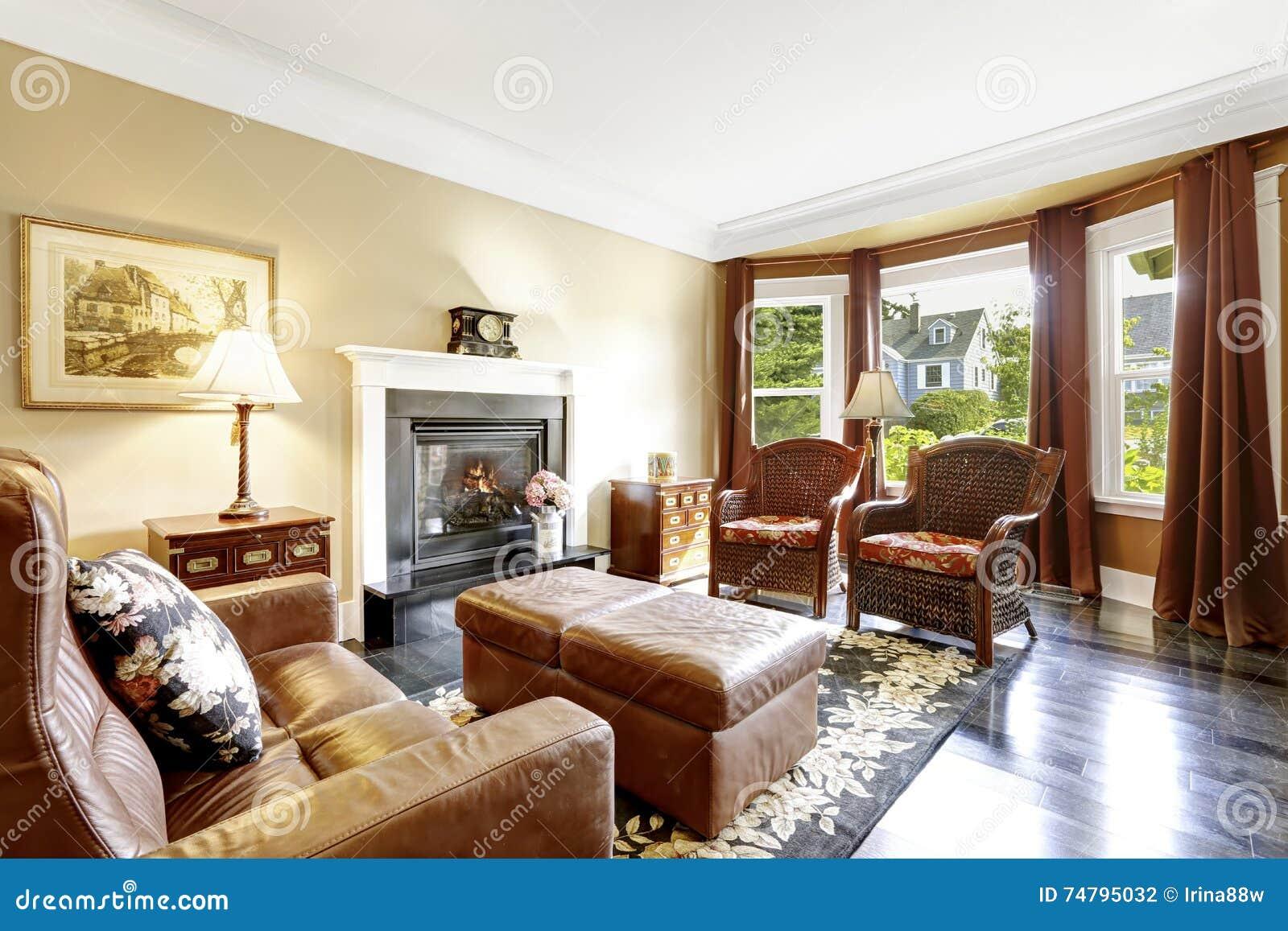 Interior home luxuoso com chaminé, as cadeiras antigas e o sofá de couro