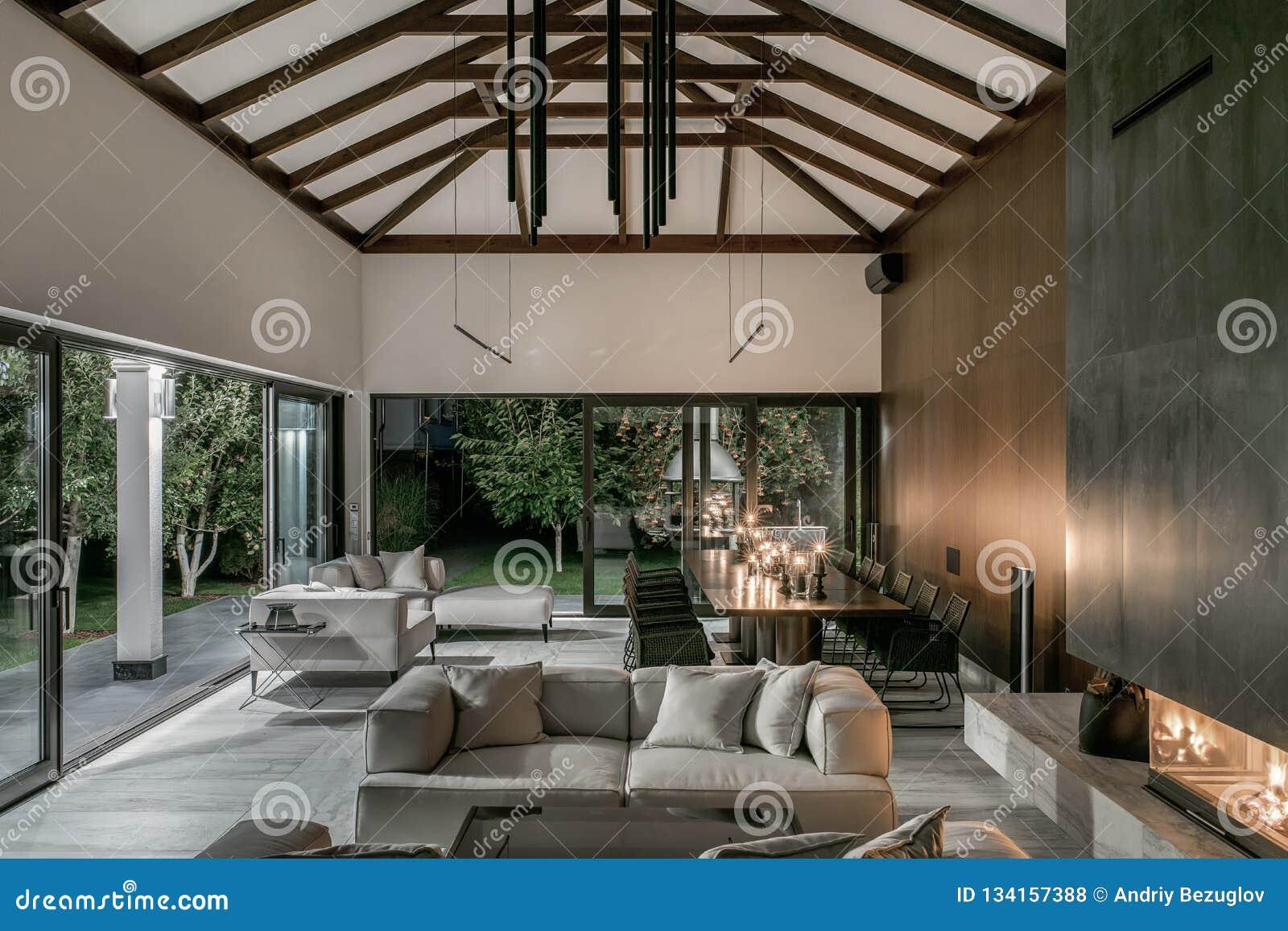Interior iluminado con los haces de madera y la chimenea