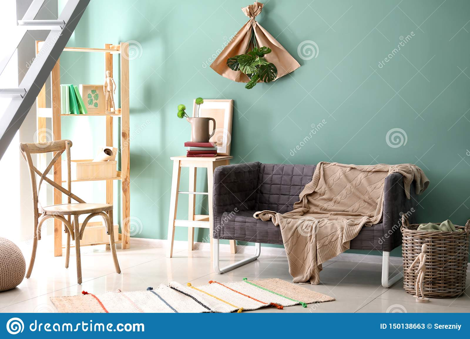 Interior of living room with comfortable sofa near color wall