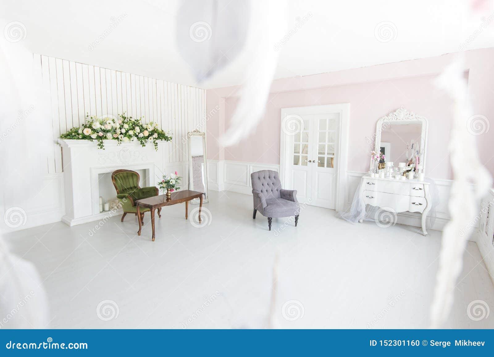 Interior lujoso brillante de la sala de estar con la chimenea y las butacas adornadas con las flores