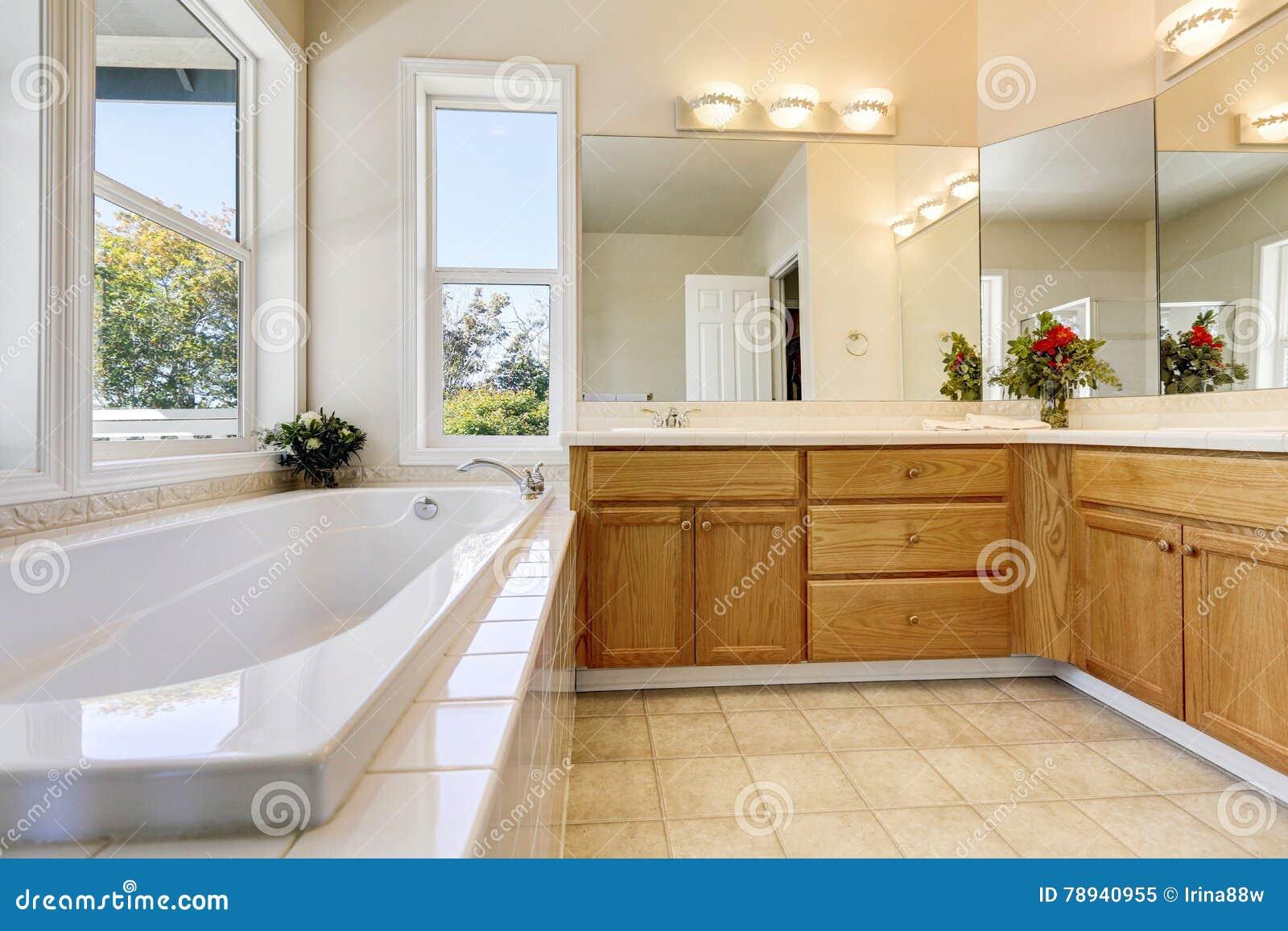Interior luxuoso do banheiro com armários de madeira e a banheira branca