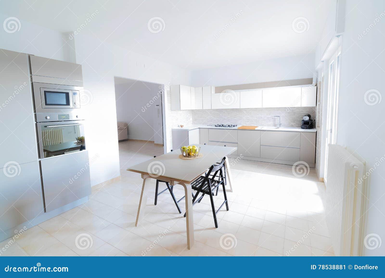 Interior moderno, brillante, limpio, de la cocina con los dispositivos del acero inoxidable y manzana del friut en la tabla en un