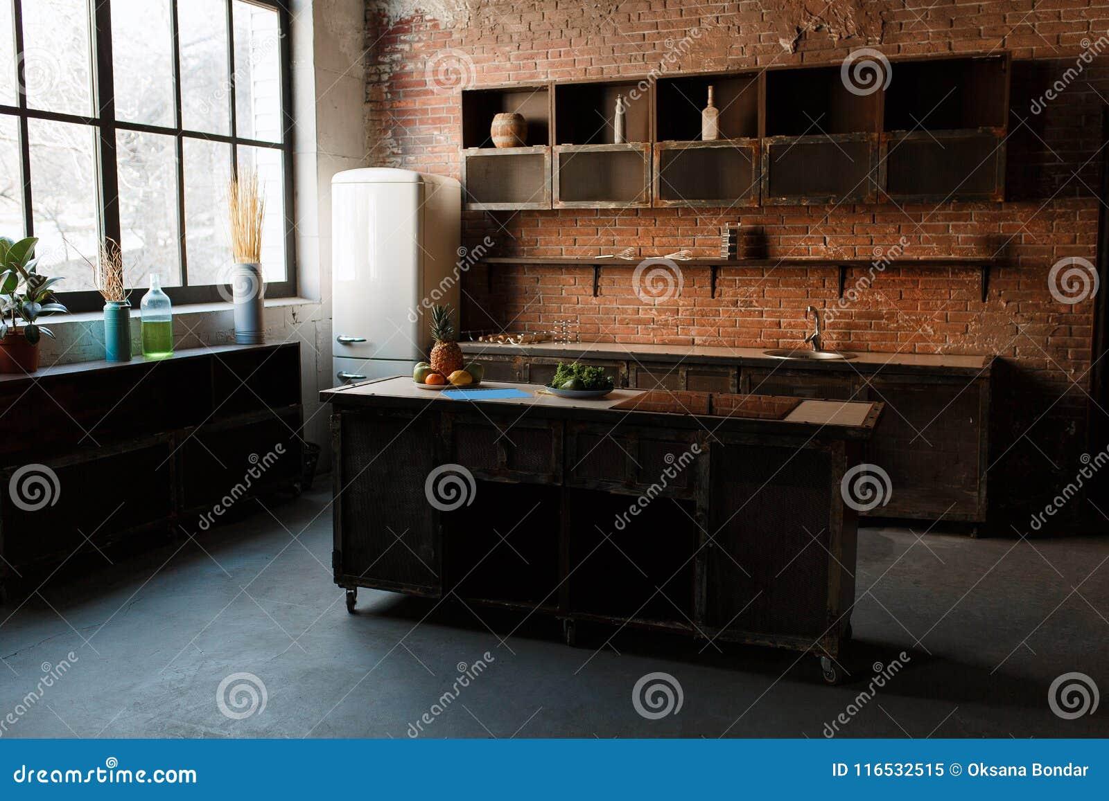 Interior moderno de la cocina con la pared de ladrillo roja, la ventana grande y la tabla de madera