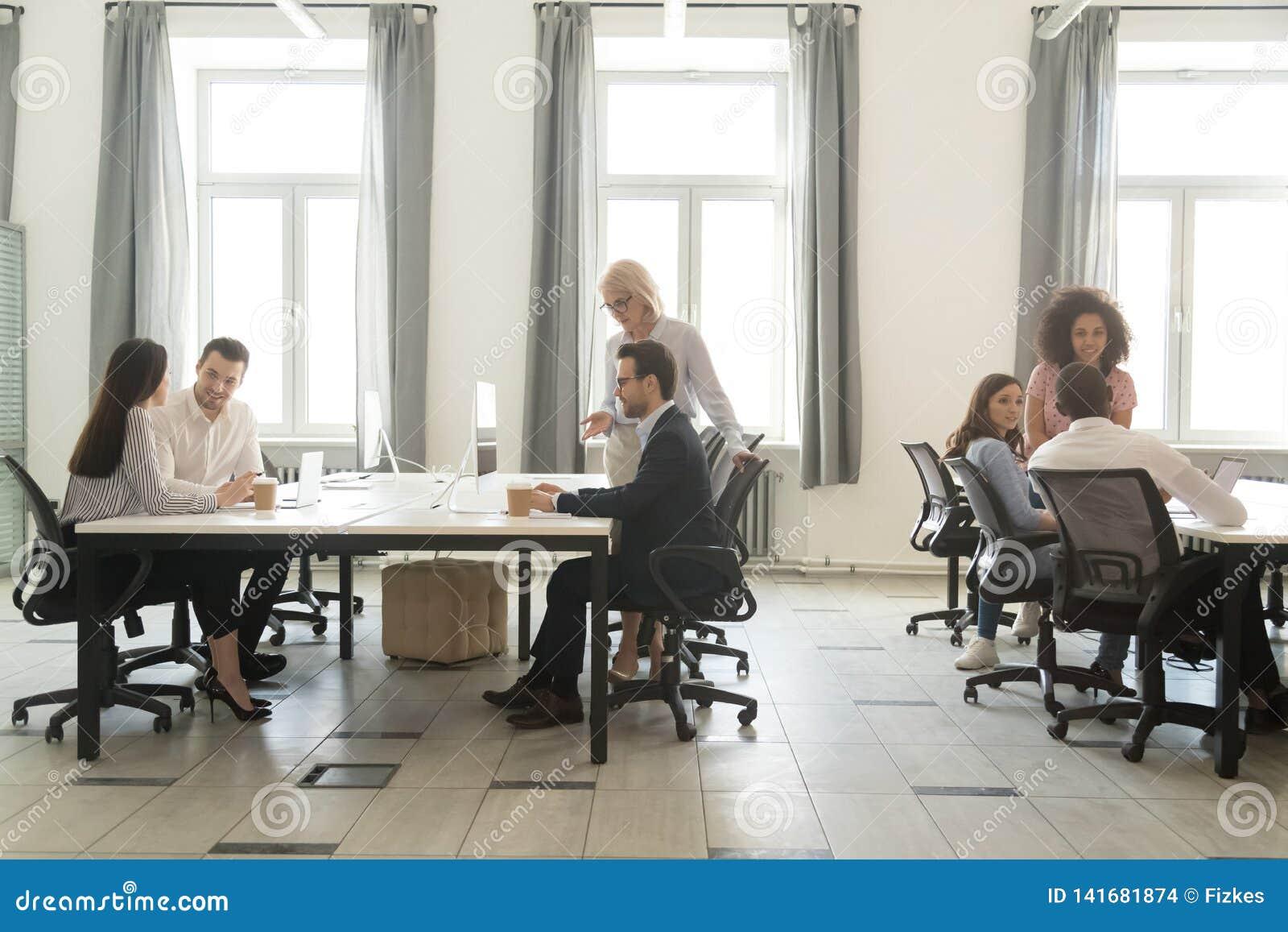 Interior moderno de la oficina con la gente del equipo del negocio que trabaja en los ordenadores