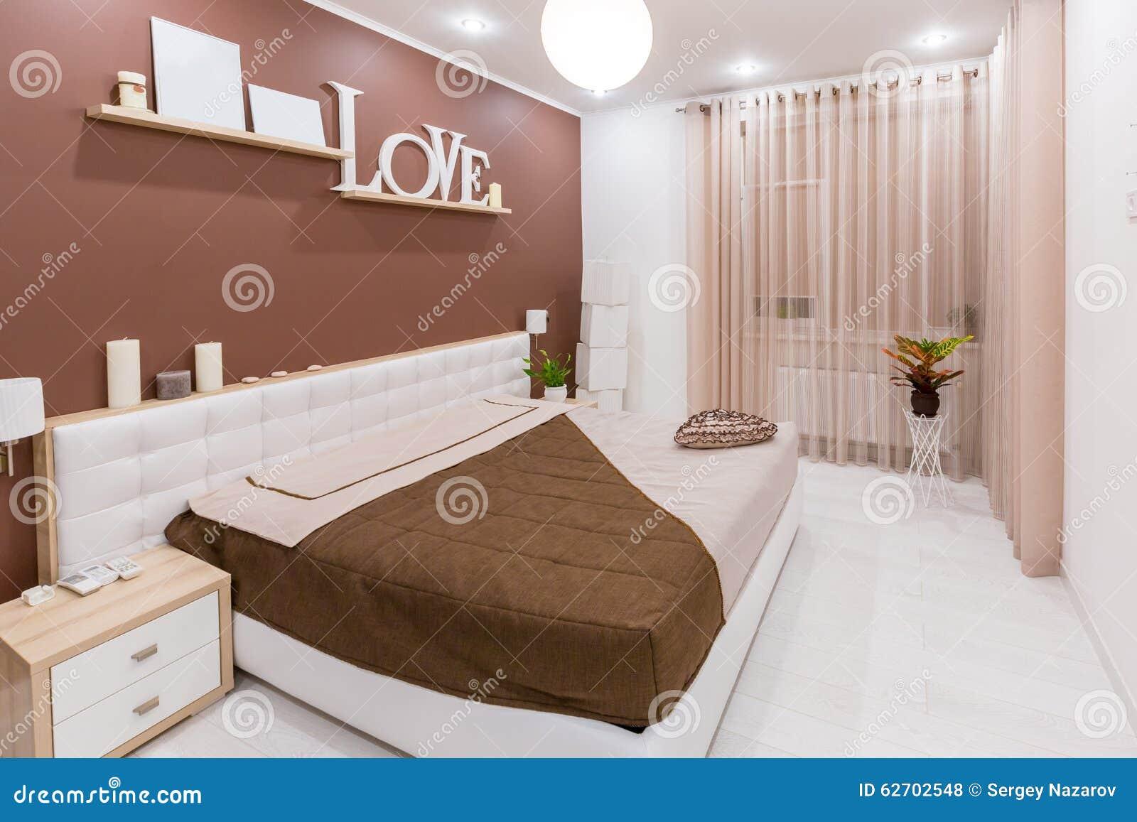 Interior moderno del dormitorio del estilo del minimalismo en tonos calientes ligeros