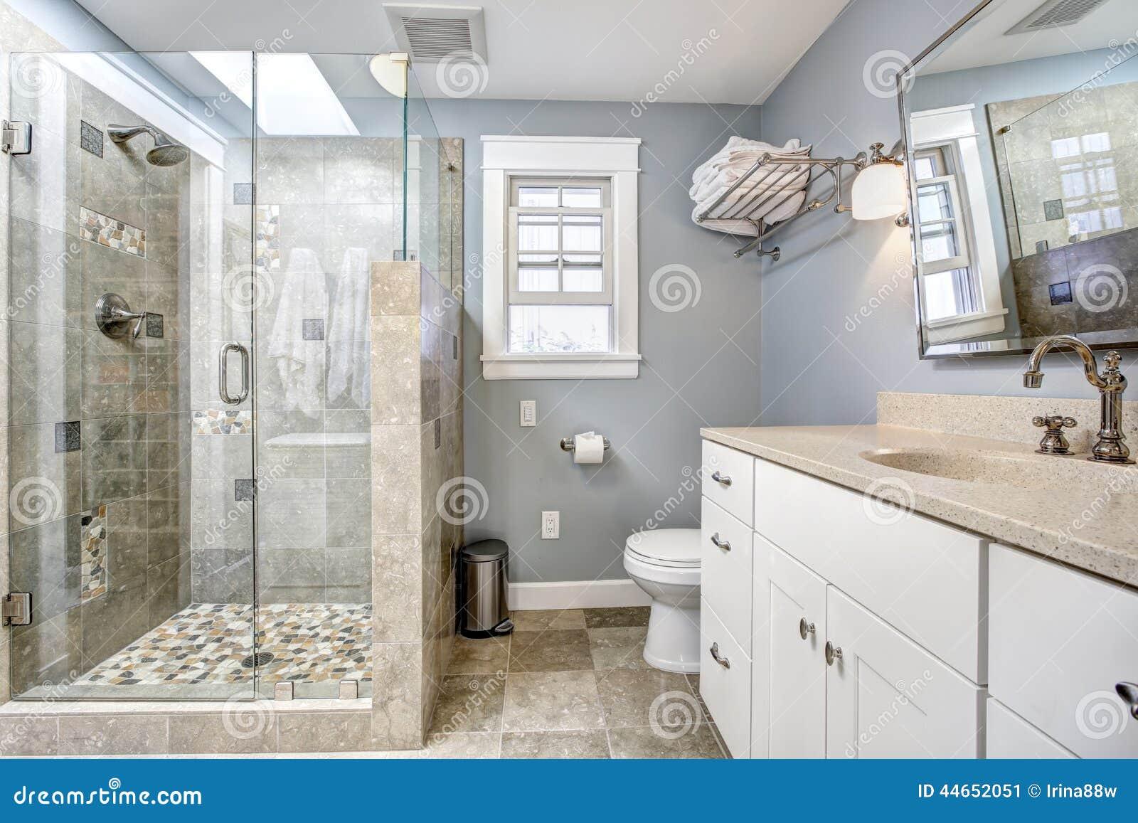 Interior moderno do banheiro com o chuveiro de vidro da porta