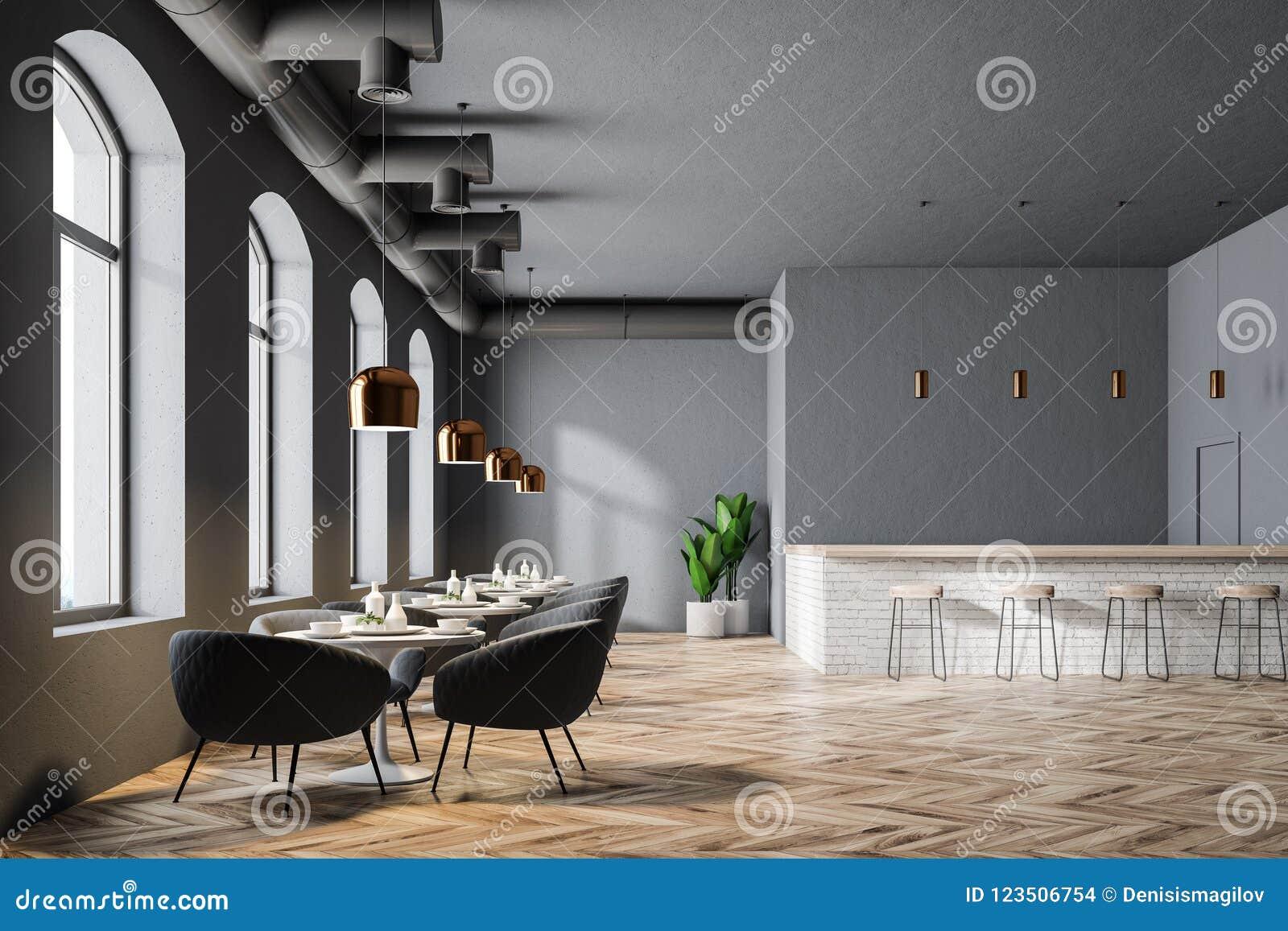 9ca801164833 Interior moderno del restaurante con las paredes grises, las ventanas  grandes, un piso de madera y las mesas redondas con las butacas Una barra  con los ...