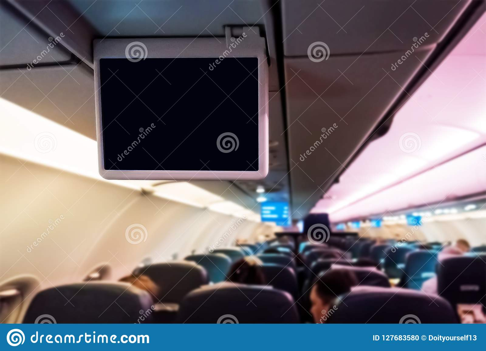 Interior of passenger airplane and blank entertainment screens
