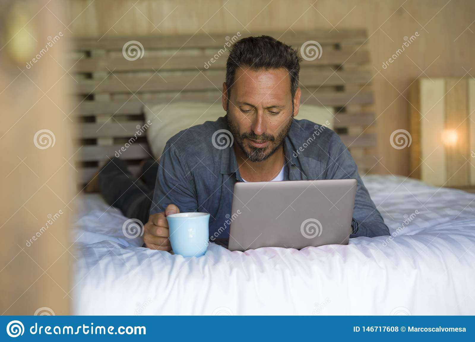 Interior portrait of young attractive and happy man at home working relaxed on bed with laptop computer smiling cheerful in