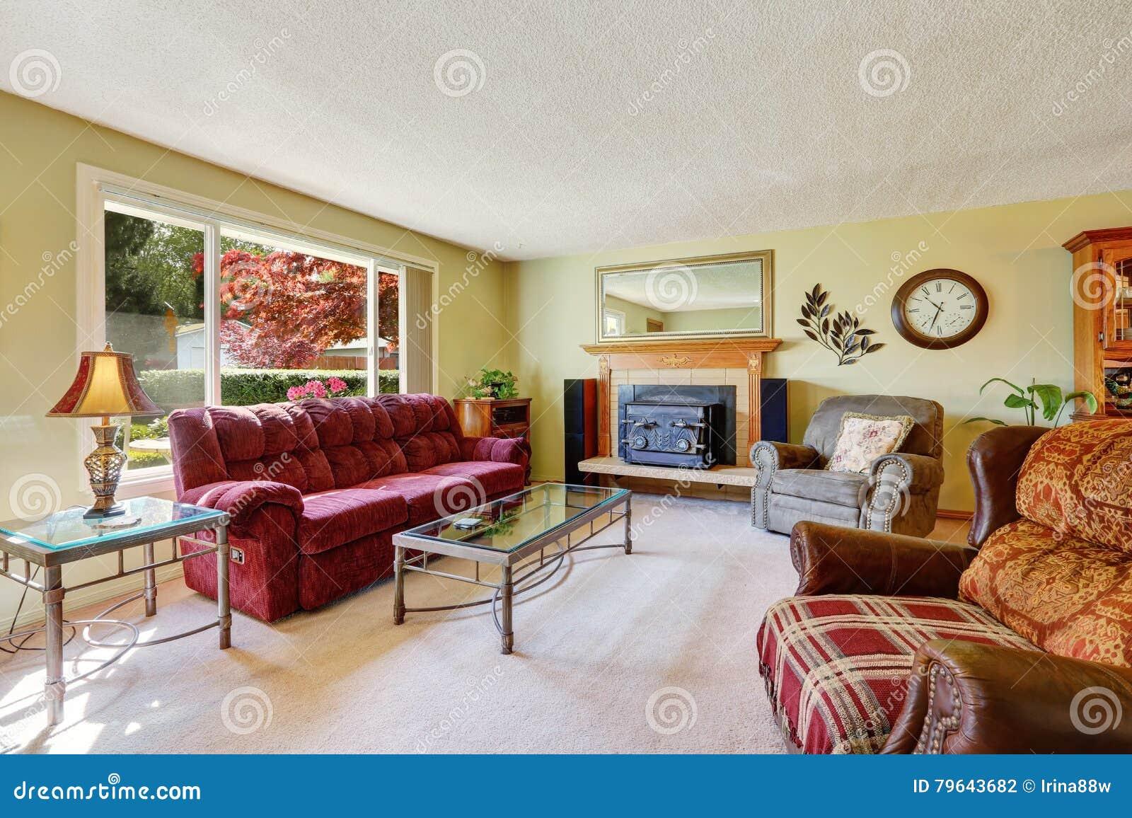 b28e766ed702b Interior retro da sala de família do estilo com o sofá vermelho confortável,  a grande janela e a chaminé do vintage Noroeste, EUA
